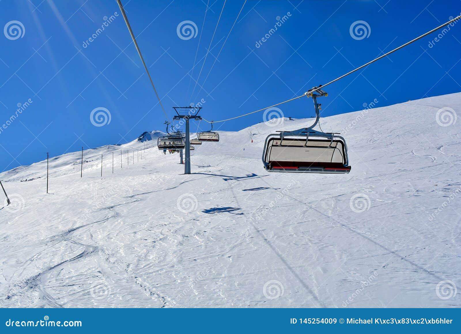 Eine Sesselbahn in den Alpen mit Sonnenschein