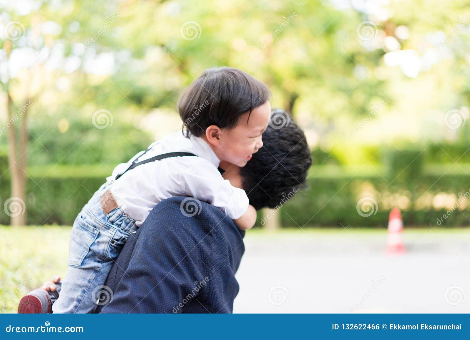 Eine Sohnumarmung sein Vater und Lächeln mit zufälliger Klage im Park