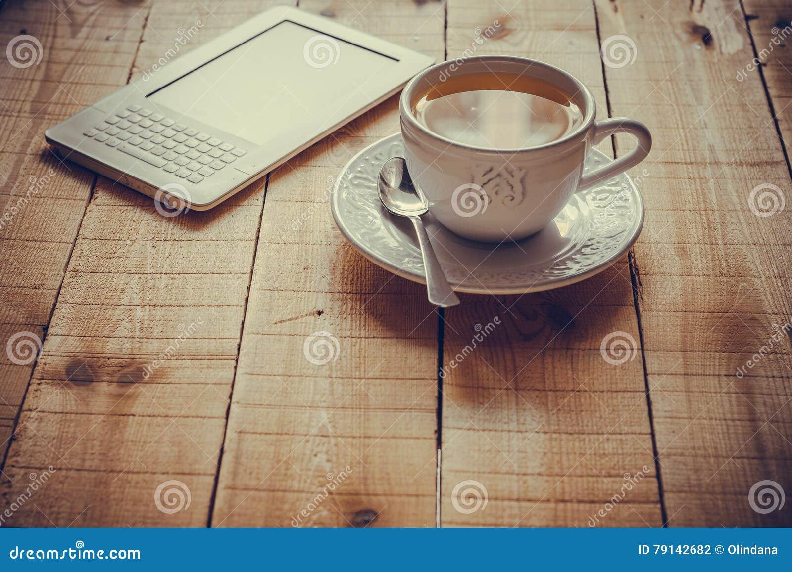 Eine Tasse Tee und ein ebook Leser auf einer hölzernen Tabelle