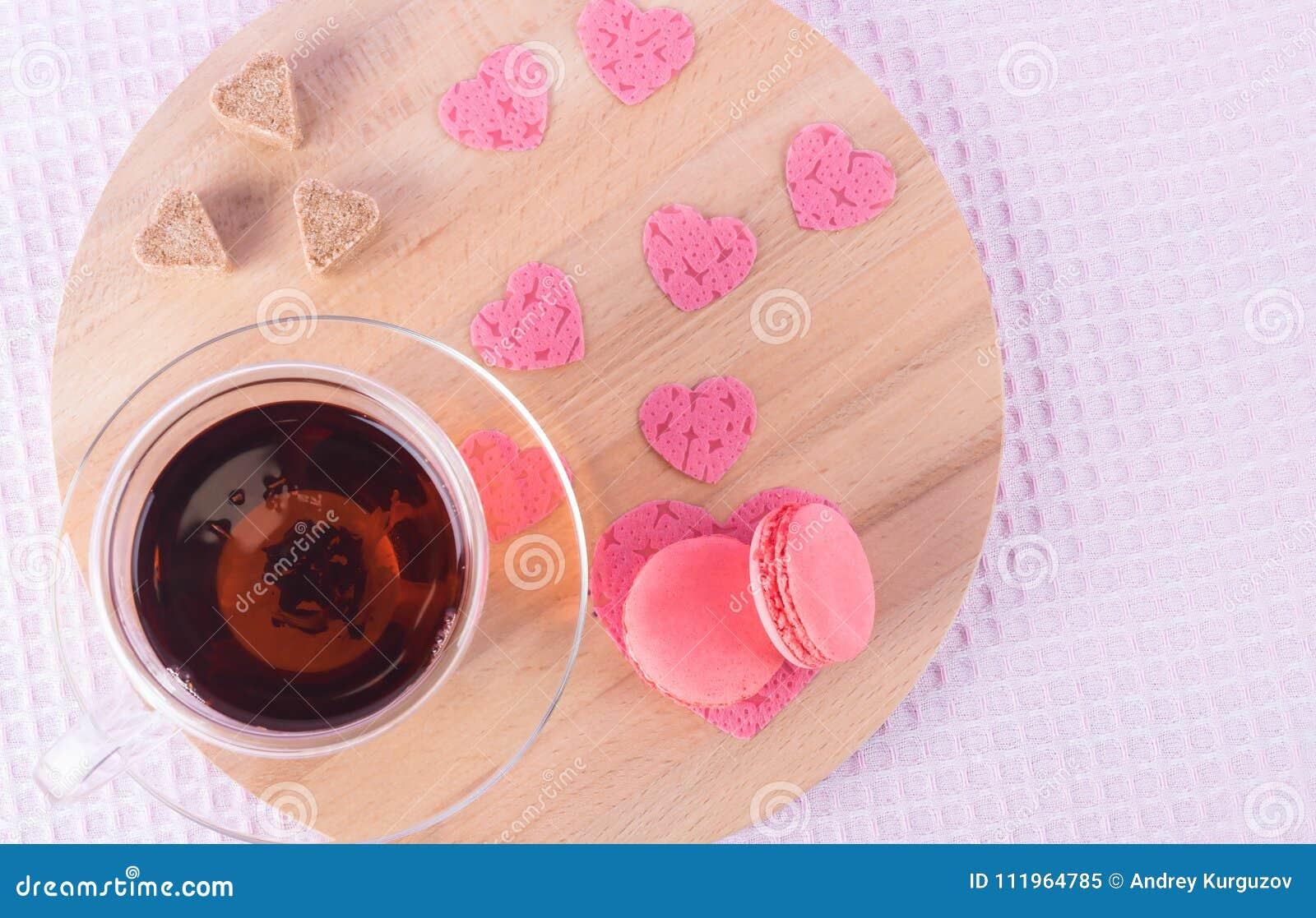 Eine Tasse Tee und eine Untertasse mit Erdbeerplätzchen zusammen mit Zuckerherzen und rosa Herzen auf einem hellen runden hölzern