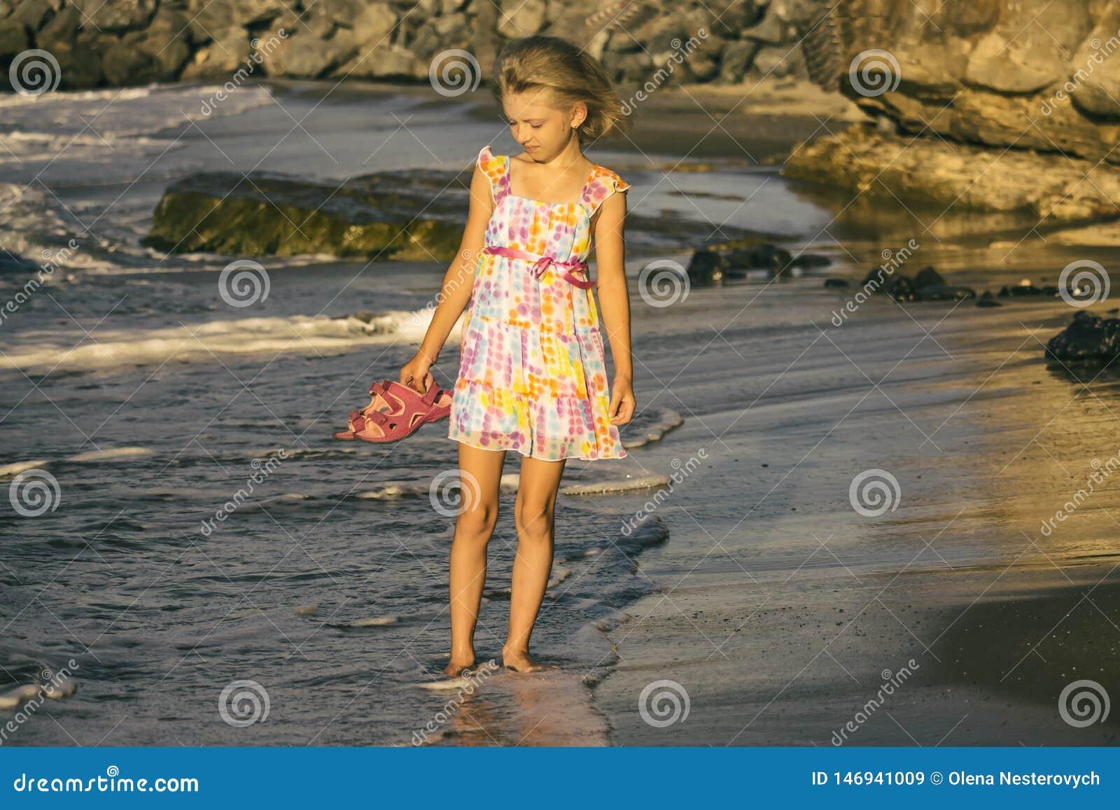 Eine träumerische Mädchenblondine in einem schönen Kleid geht entlang das Ufer, Weichzeichnung