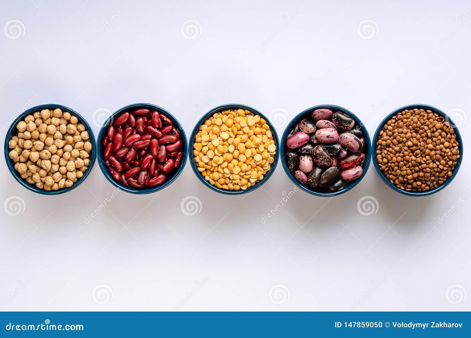 Eine Vielzahl von H?lsenfr?chte Linsen, Kichererbsen, Erbsen und Bohnen in den blauen Sch?sseln auf einem wei?en Hintergrund Besc