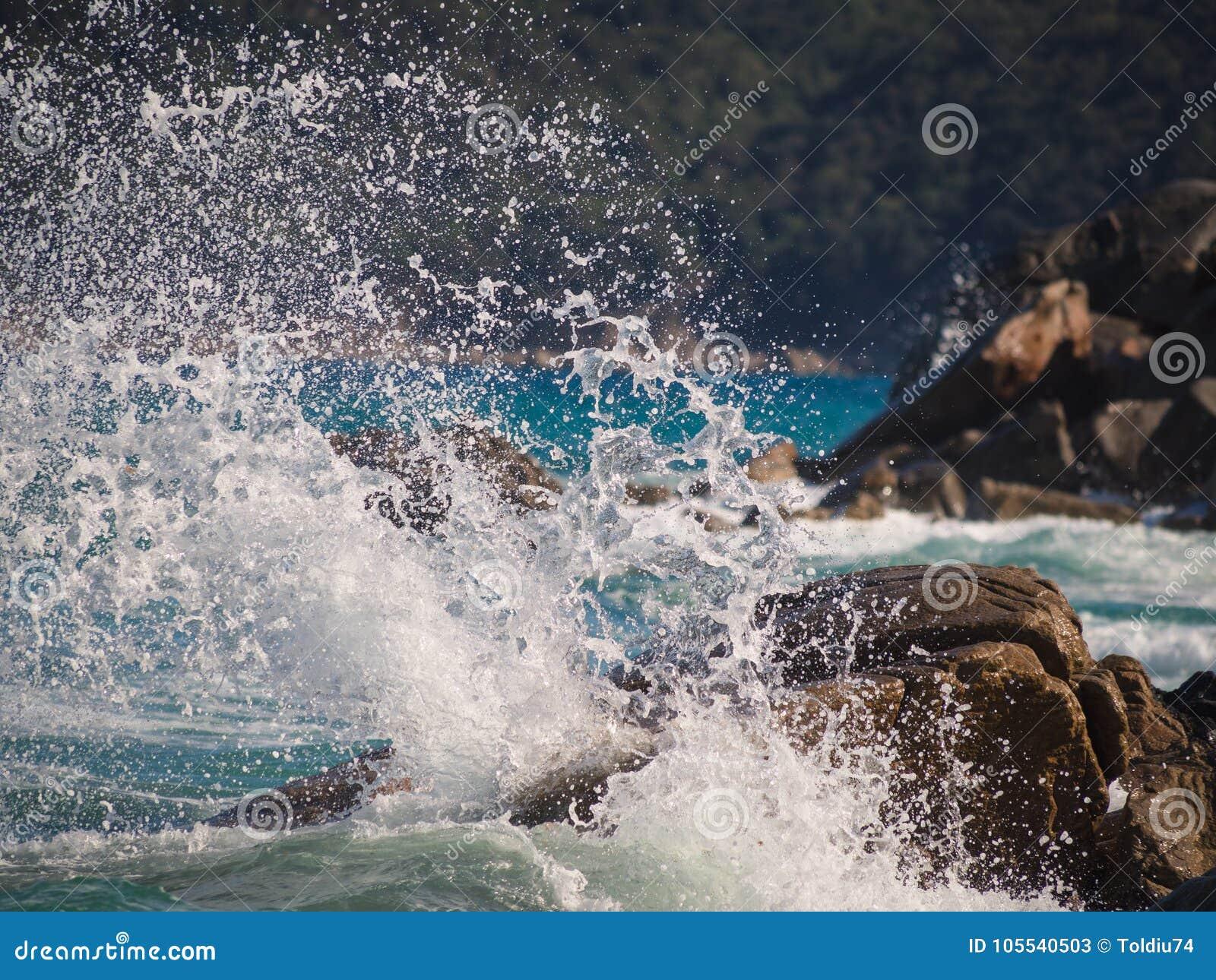 Eine Welle, die auf den Felsen bricht