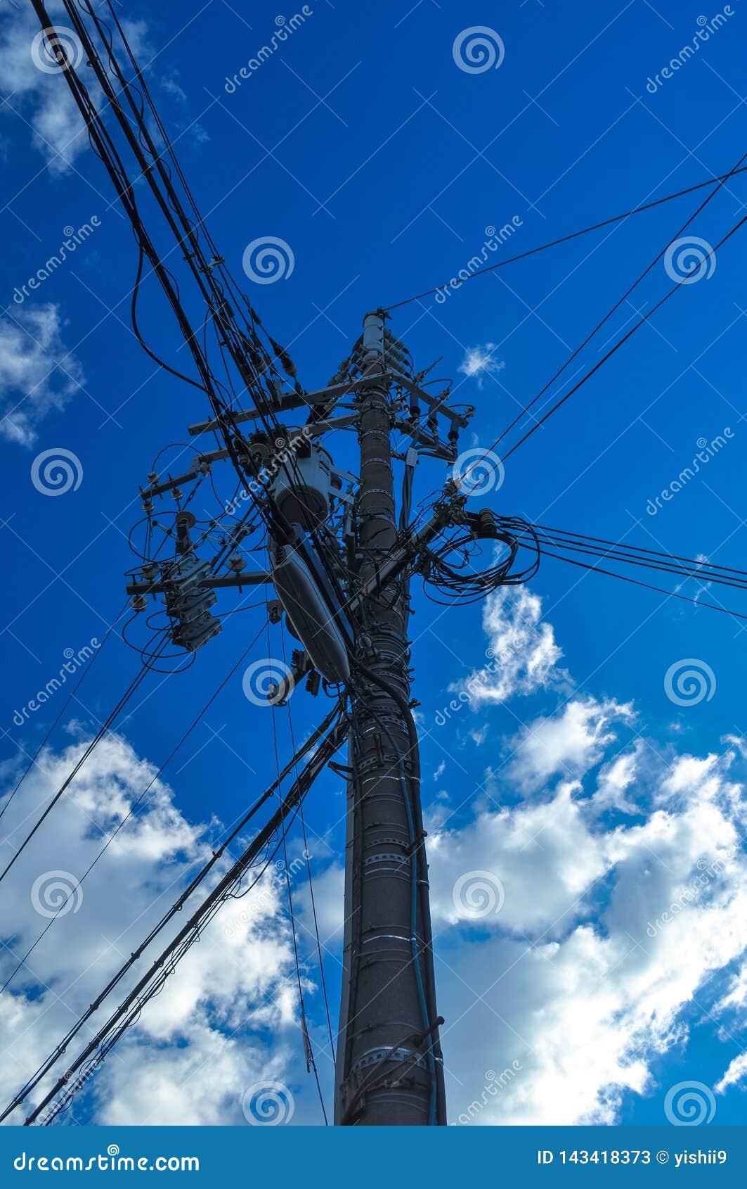 Einen Strommast mit blauem Himmel im Hintergrund oben schauen