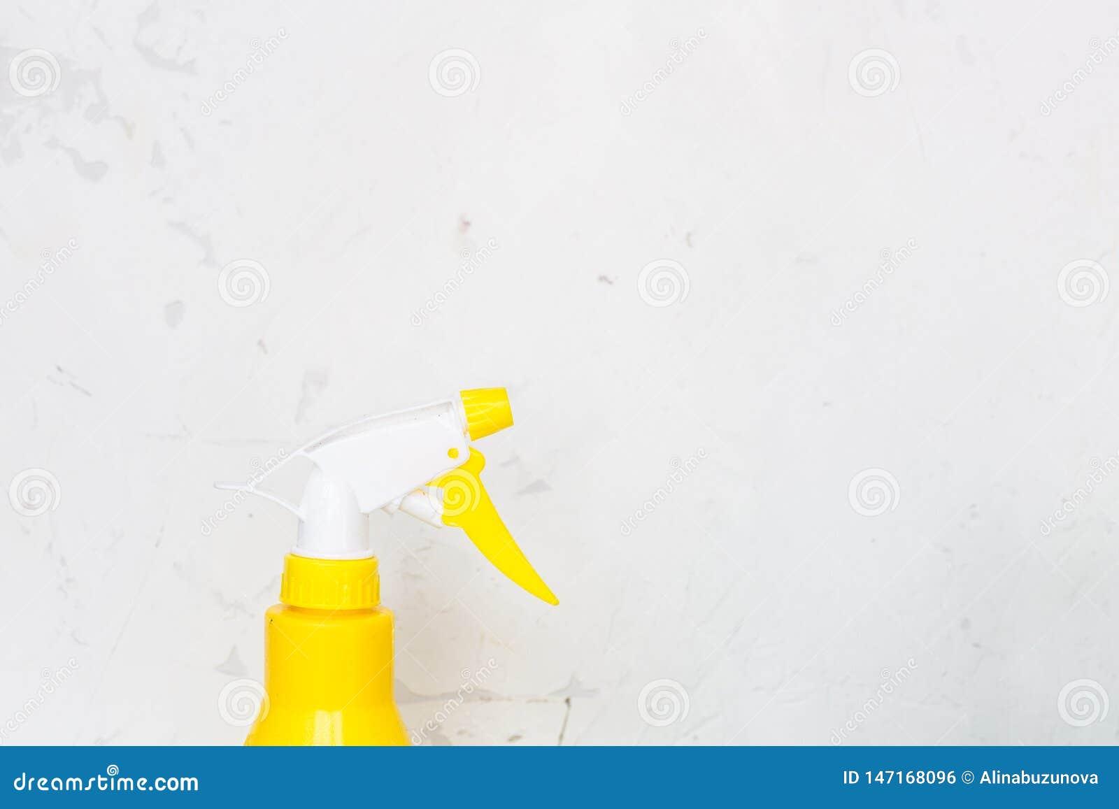 Einfache gelbe Plastikhandsprühflasche auf grauem Hintergrund