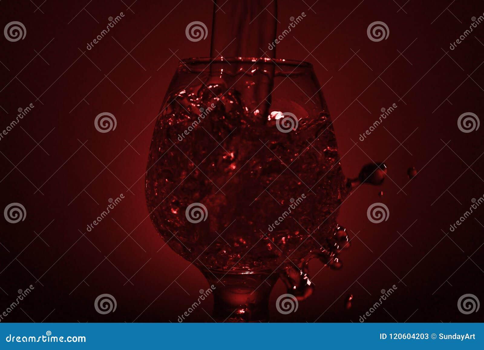 Einfaches Stilllebenfoto Whiskyglas-, Wasserstrahl- und schwachemrotes L