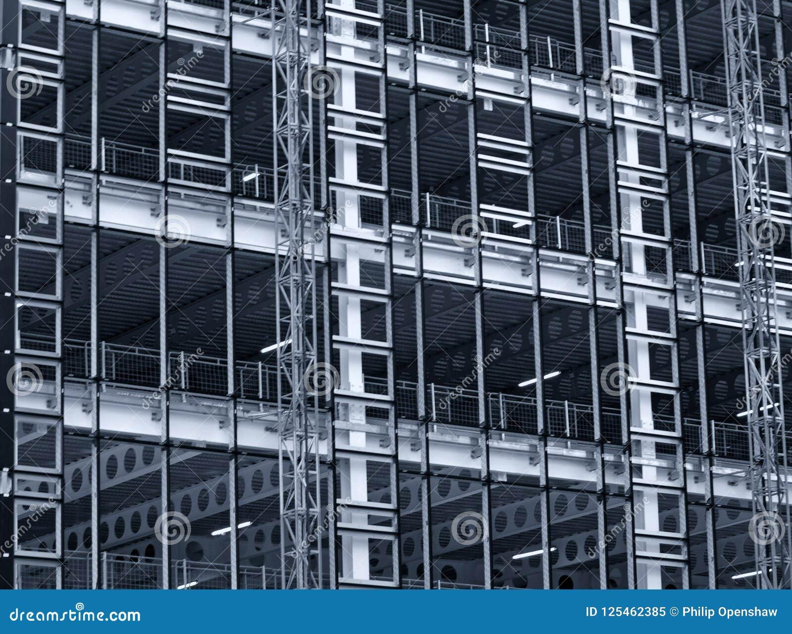 Einfarbige blaue abgetönte Ansicht einer großen errichtenden Entwicklung im Bau mit Stahlgerüst und Trägern