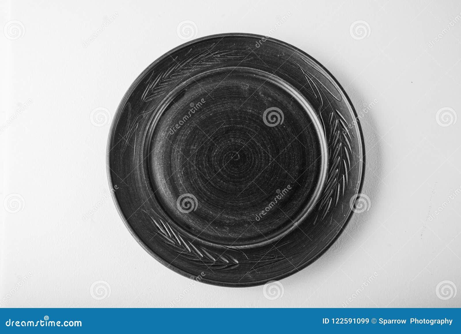 Einfarbiges Bild Draufsicht einer schwarzen Pastellplatte auf einem weißen Pastellhintergrund Minimalismuslebensmittelphotographi