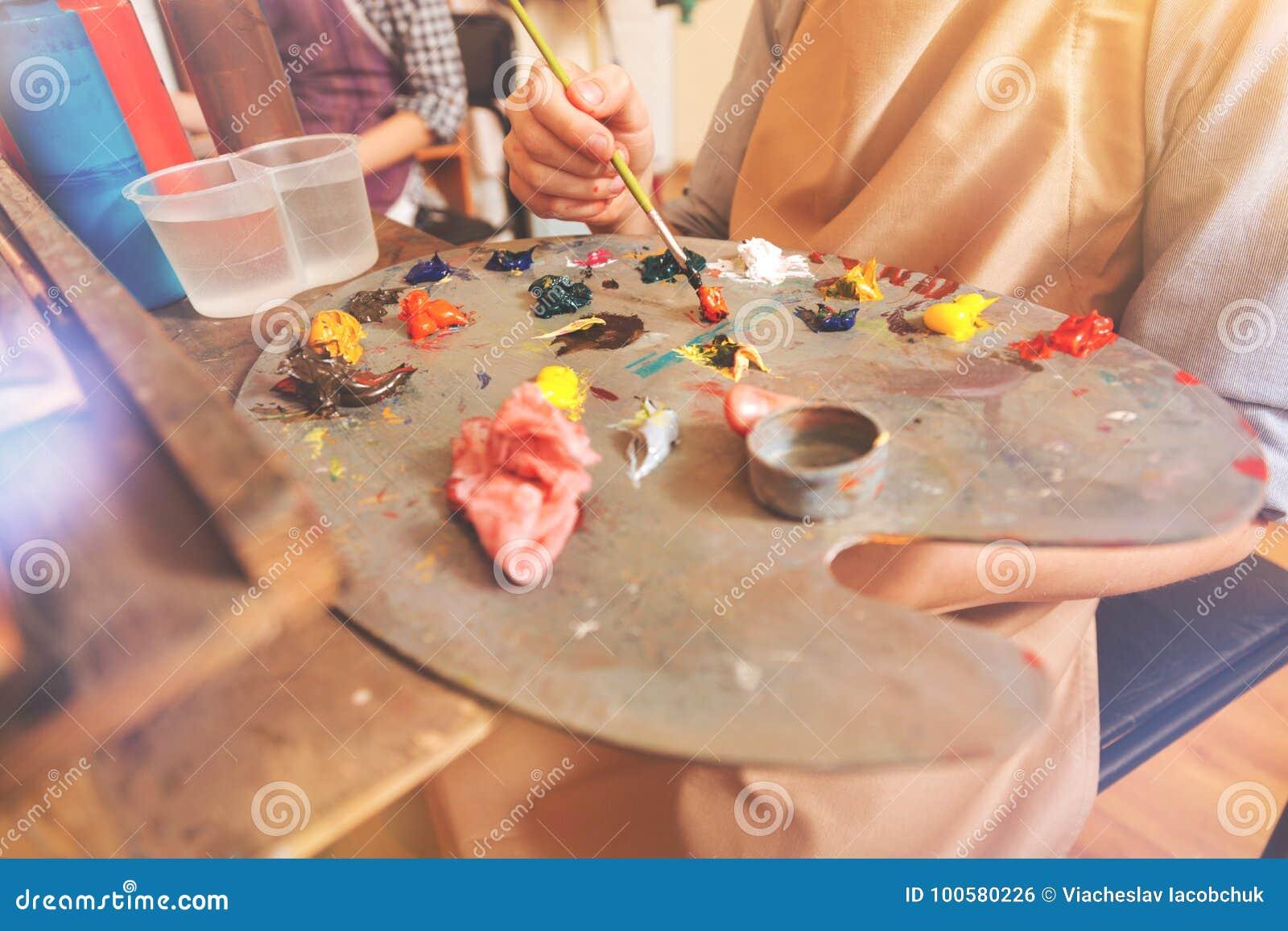Eingestuft herauf Ansicht über den Künstler, der helle Farben auf Palette mischt