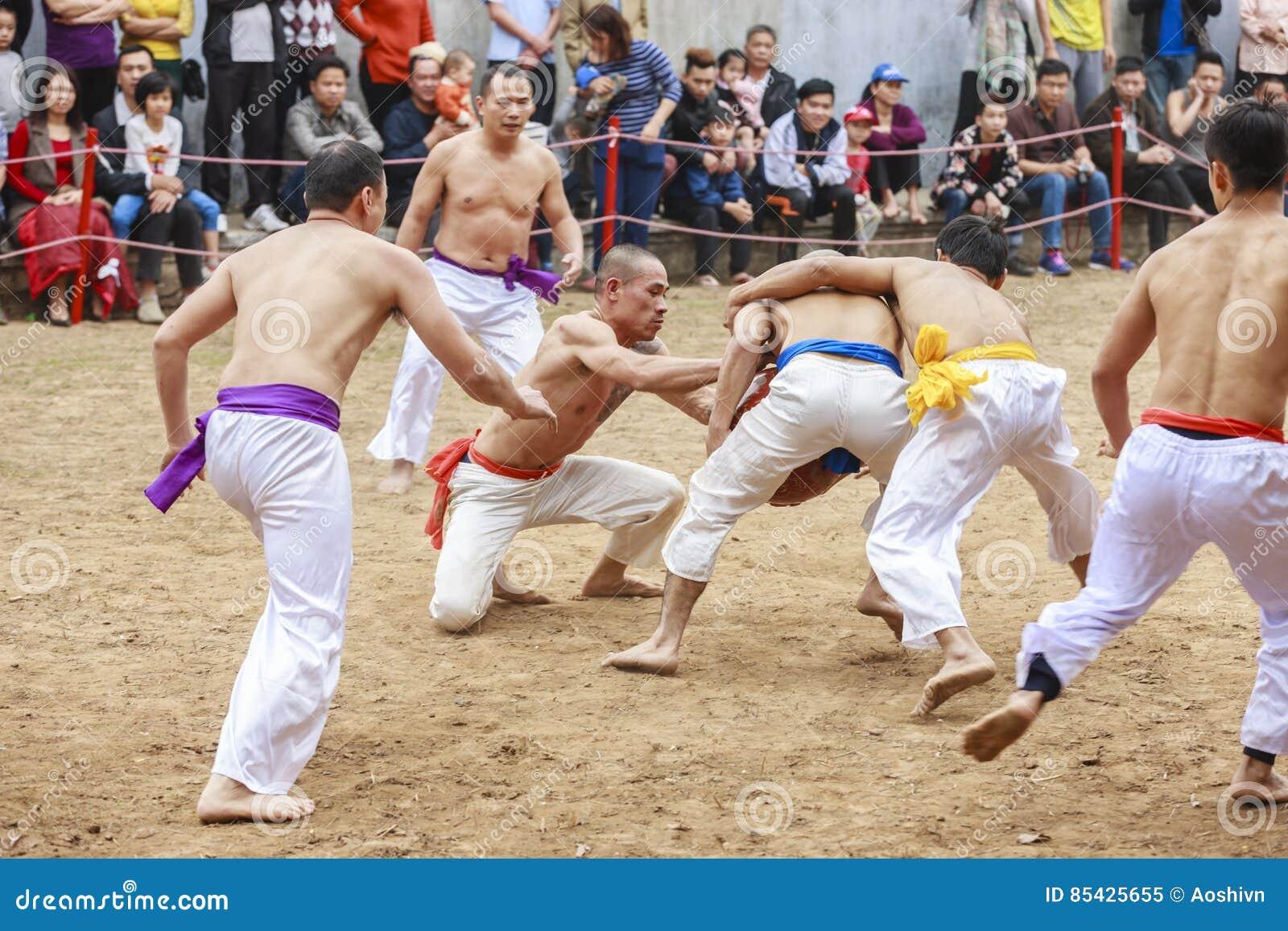 Einige junge Männer spielen mit hölzernem Ball im neuen Mondjahr des Festivals in Hanoi, Vietnam am 27. Januar 2016