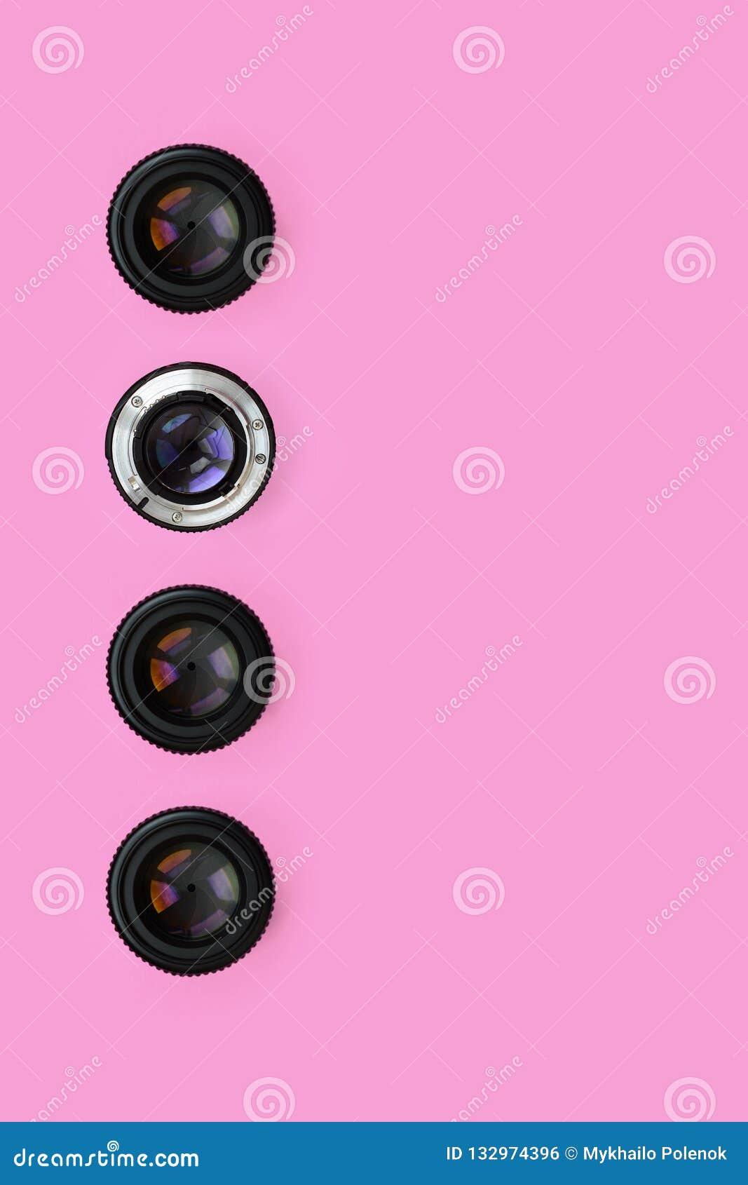 Einige Kameraobjektive mit einer geschlossenen Öffnungslüge auf Beschaffenheitshintergrund des rosa Pastellpapiers der Mode Farbi