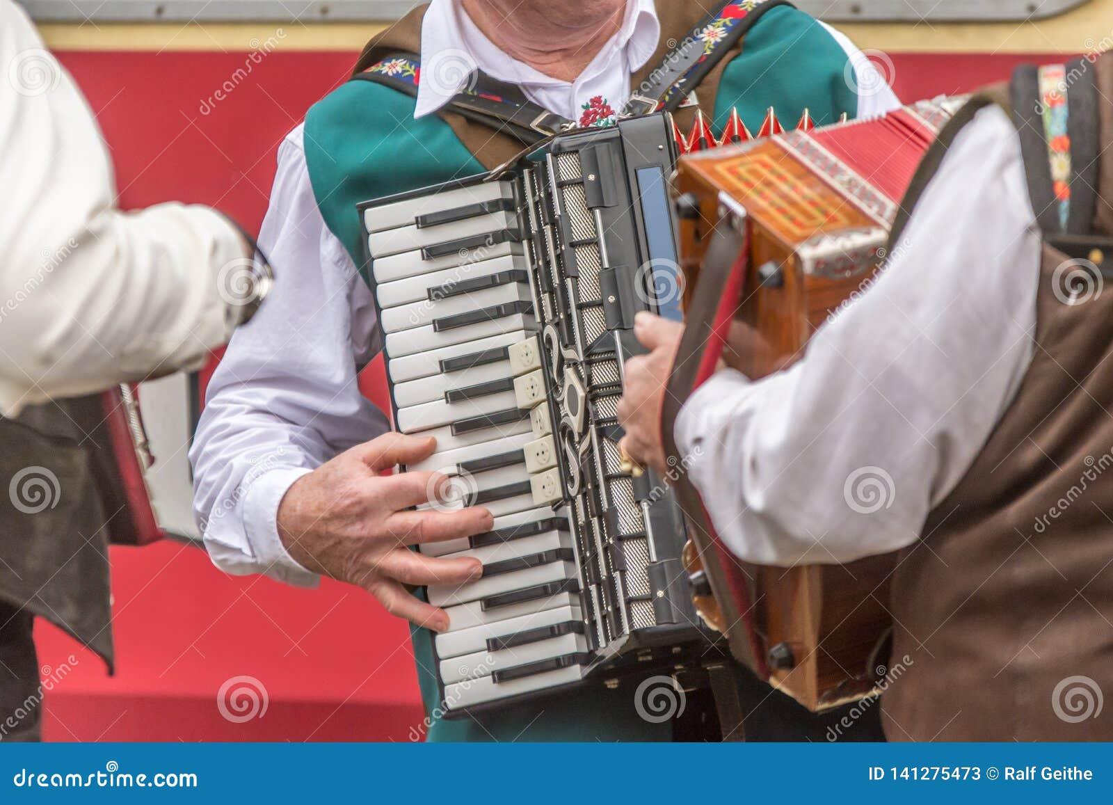 Einige Männer in der traditionellen Kleidung spielen das Akkordeon