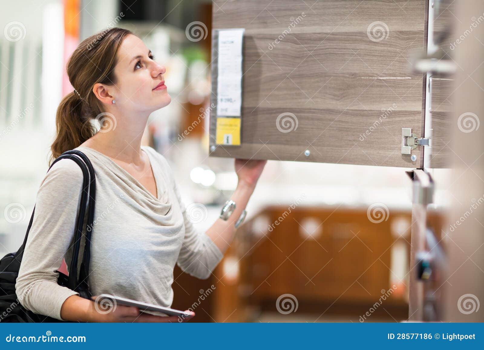 Einkaufen der jungen Frau für Möbel in einem Möbelgeschäft