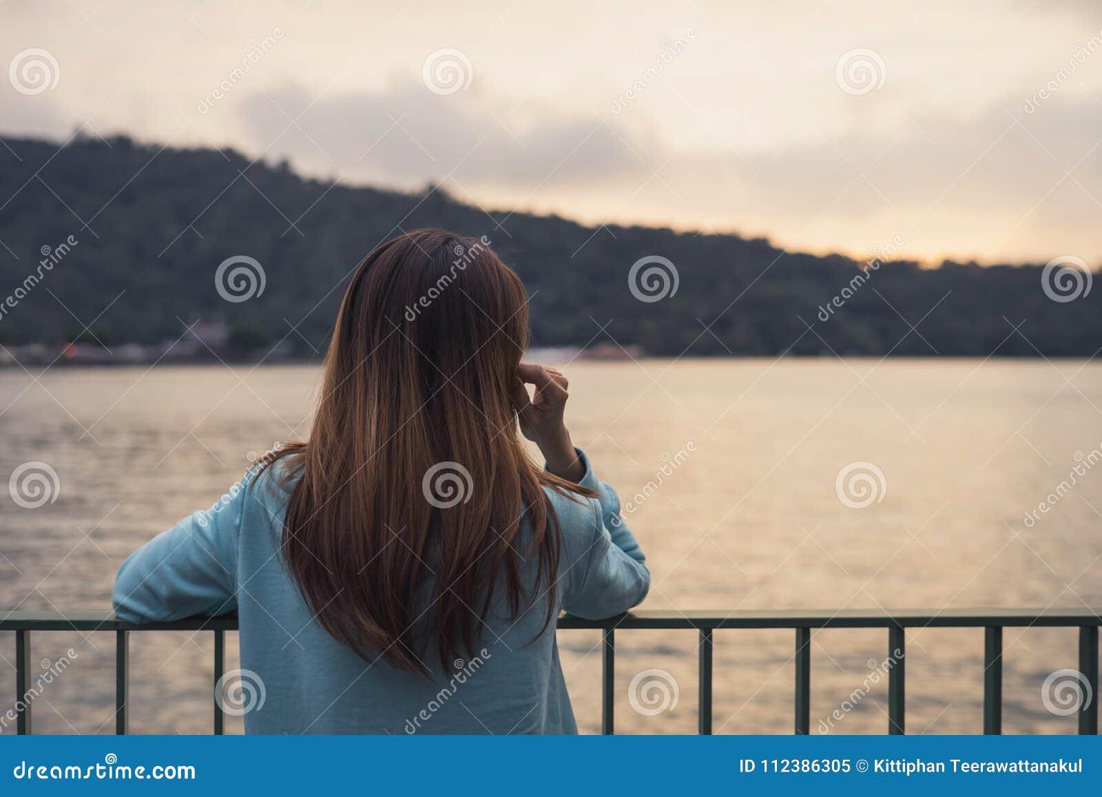 Einsame Frau, die abwesendes gekümmert in dem Fluss steht