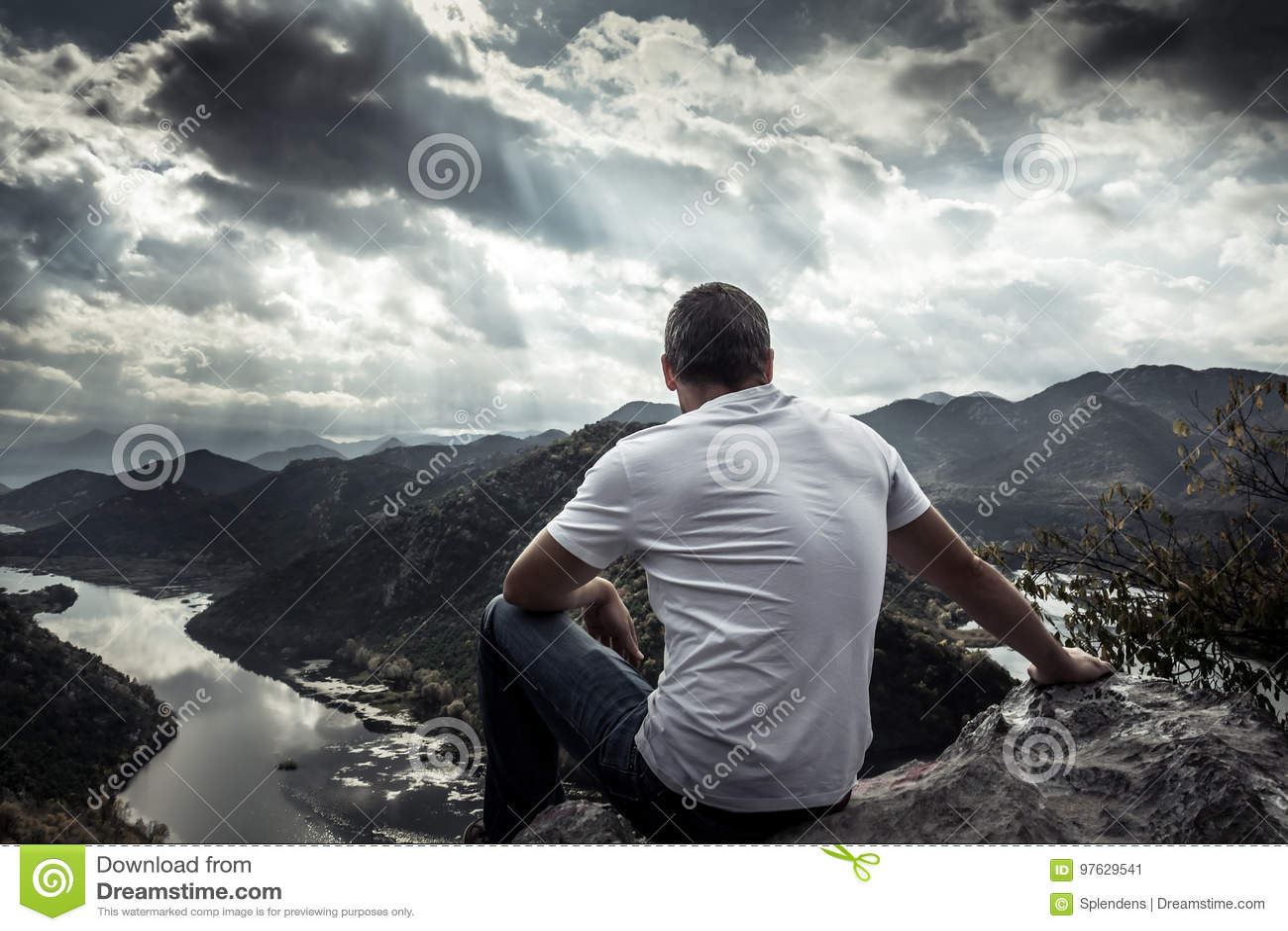 Einsamer Mann, der mit Hoffnung auf Horizont auf Bergspitze mit drastischem Sonnenlicht während des Sonnenuntergangs mit Effekt d