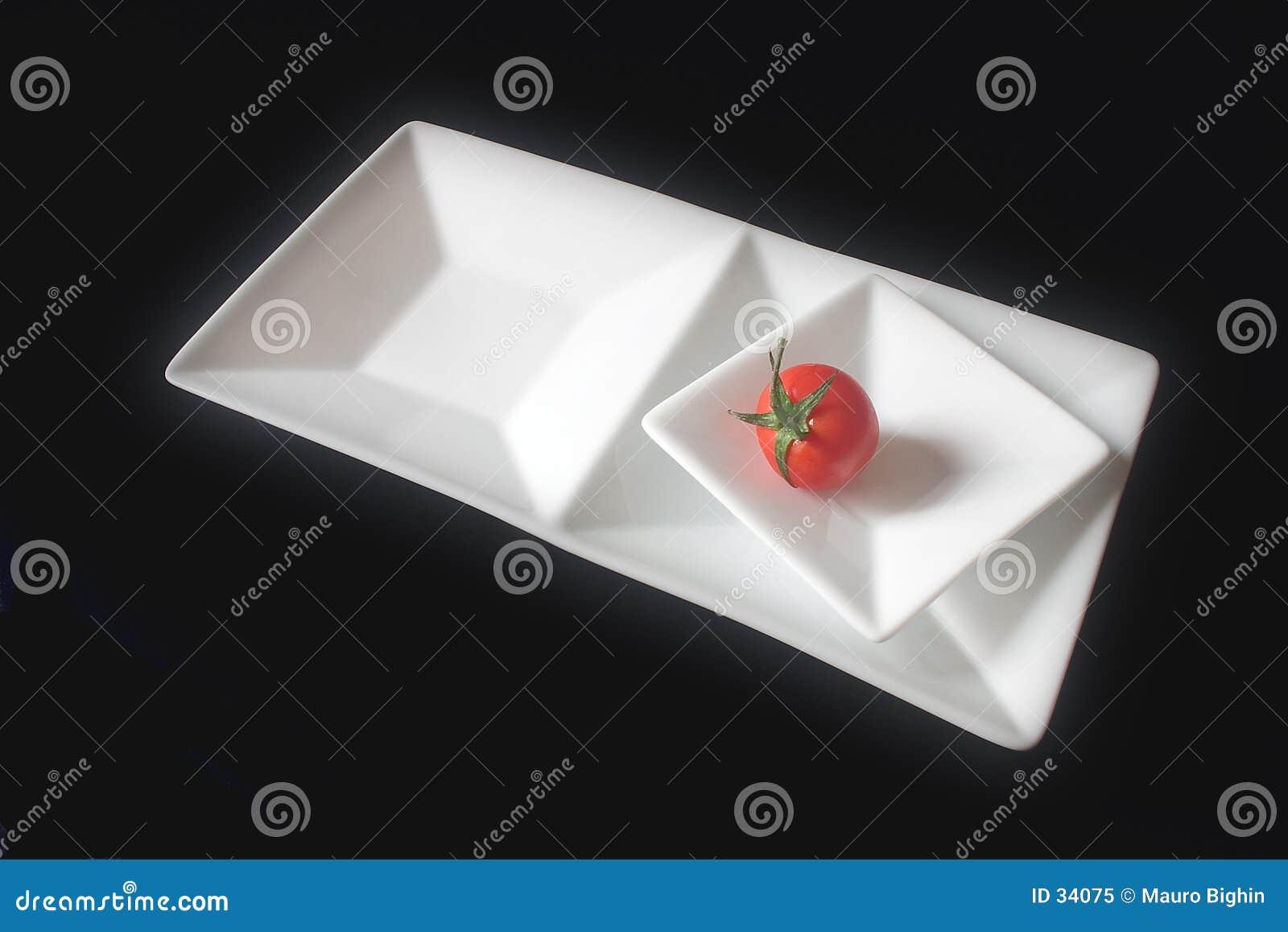 Einzelne Tomate auf quadrierten Tellern