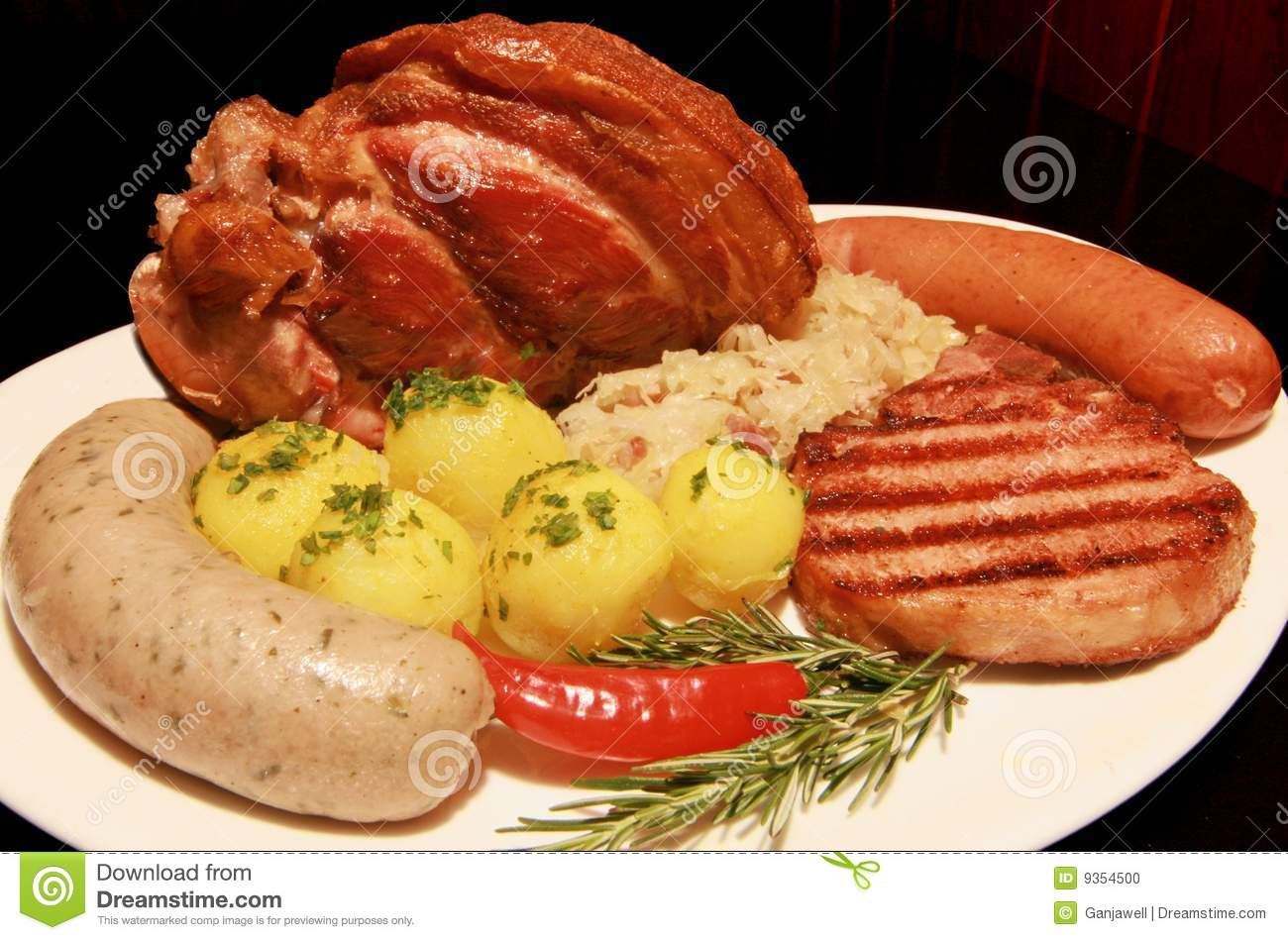 Plate of smoked roasted eisbein with german wurst sausages potatoes