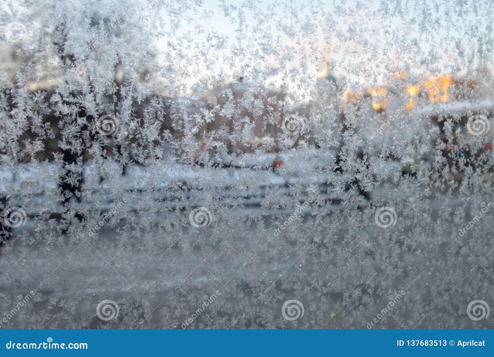 Eisblumen auf einem Glas Unscharfe Stadtansicht durch ein bereiftes Fenster Konzept von extrem Zuständen des kühlen Wetters