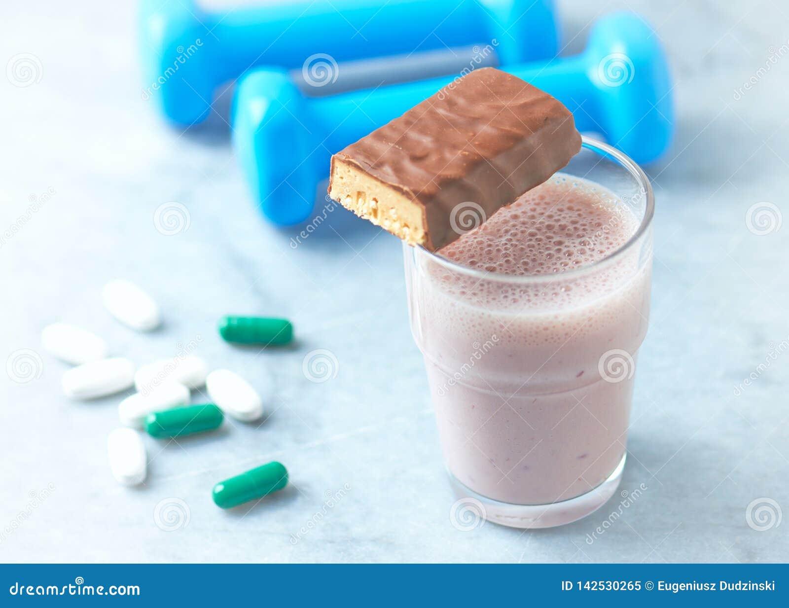 Eiwitbar, glas van eiwitschok met melk en frambozen BCAA-aminozuren, L - Carnitine capsules en blauwe domoren in rug