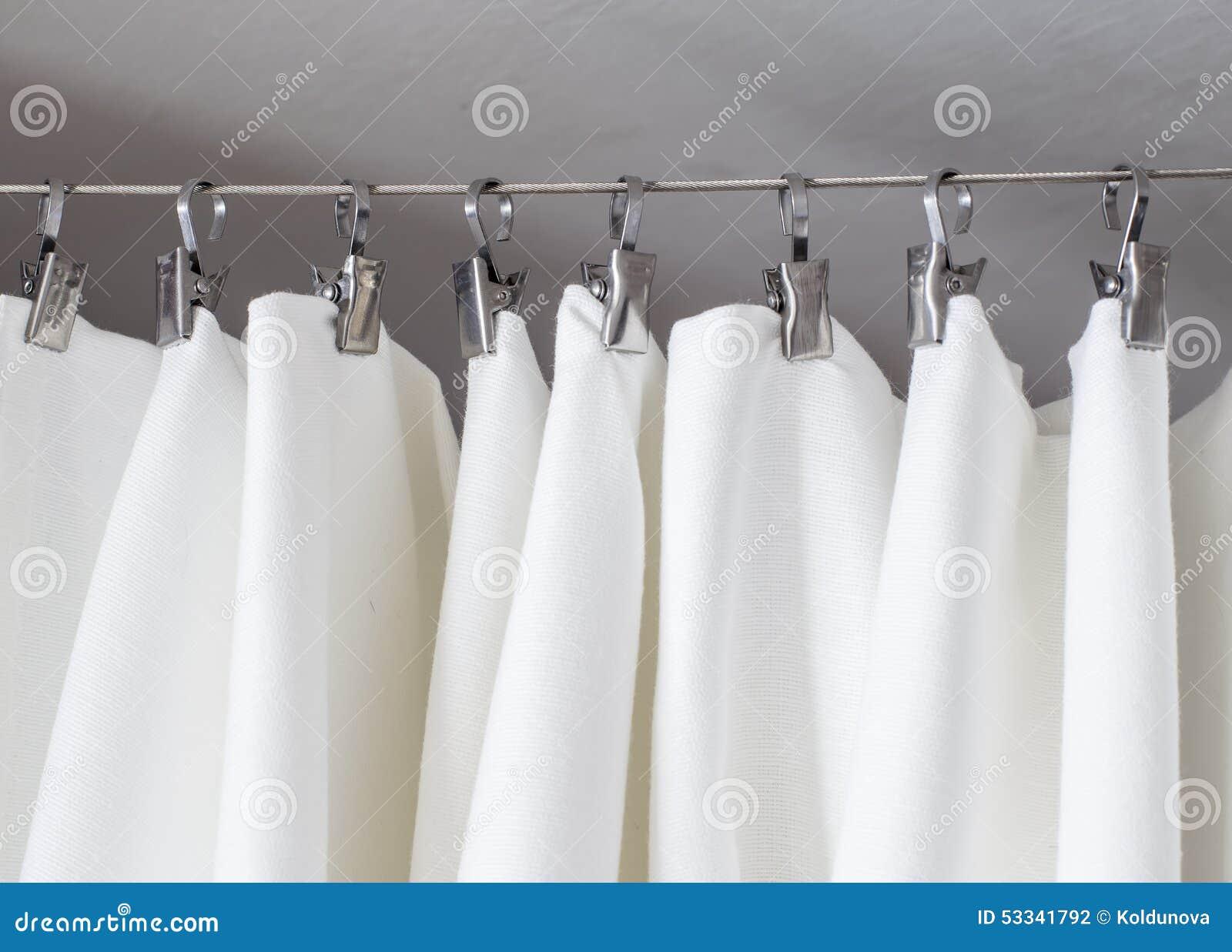 Ejecución color nata de la cortina en una secuencia en los ganchos del metal iluminados por la luz del día