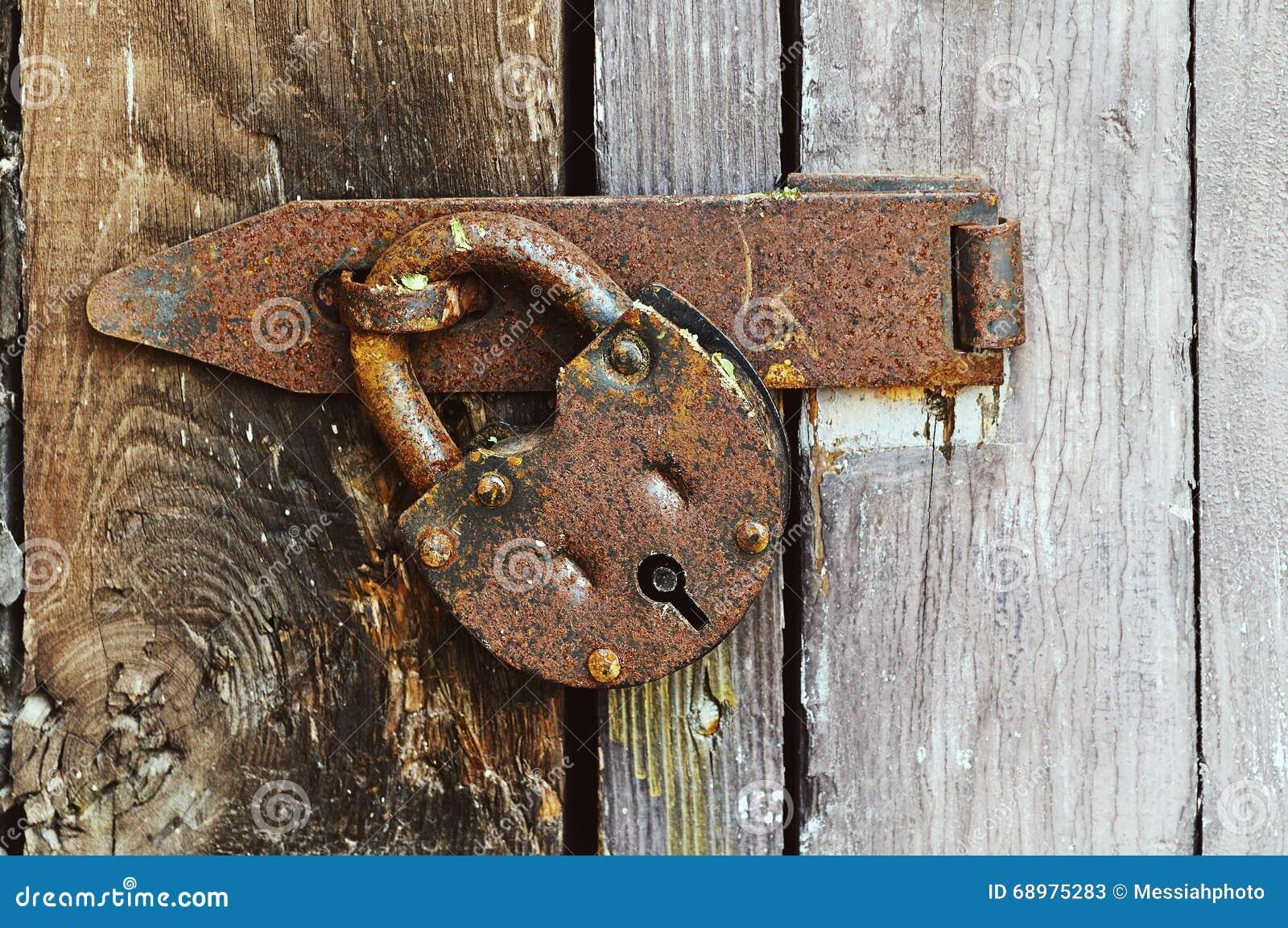Ejecución de acero oxidada del candado en la puerta resistida de madera