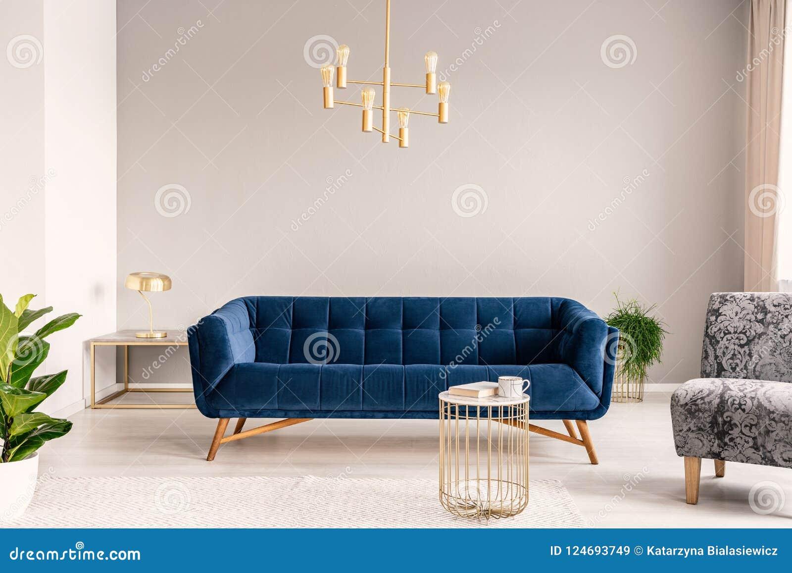 Ejecución de la lámpara del oro sobre el sofá del azul real en foto real del interior gris claro del salón con la pared vacía