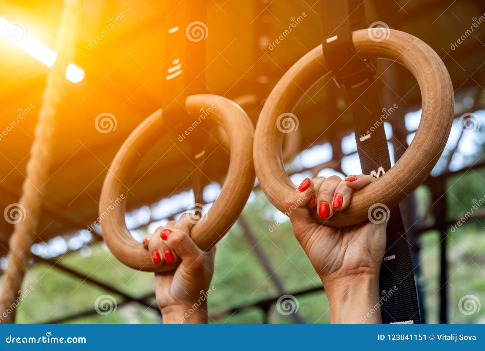 Ejecución de la mujer joven en los anillos del gimnasio