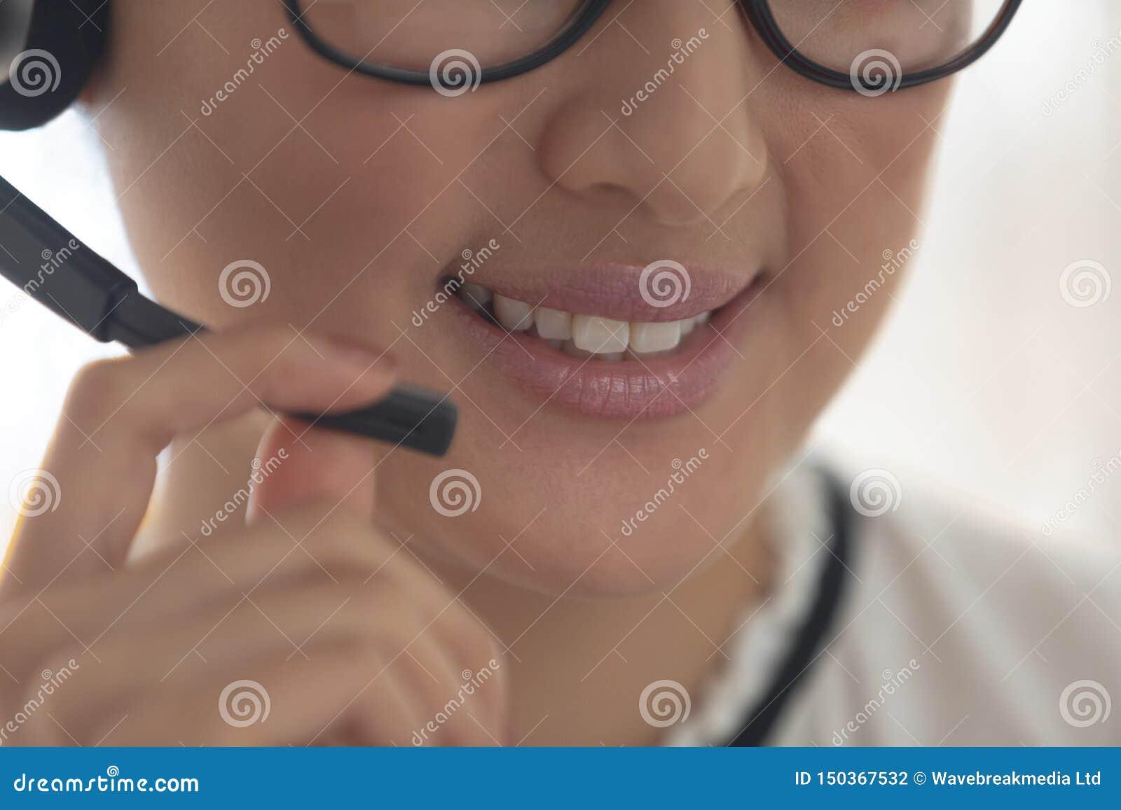 Ejecutivo de sexo femenino del servicio de atención al cliente que habla en las auriculares en una oficina moderna