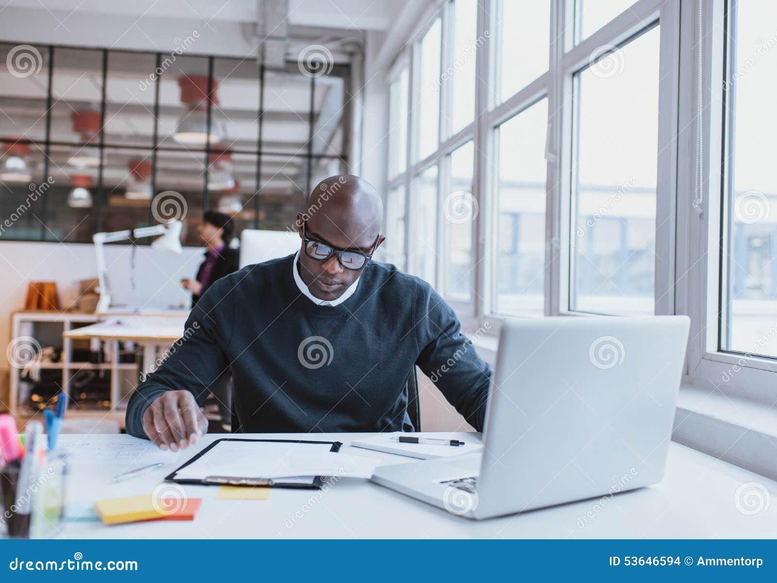 Ejecutivo joven en su escritorio que lee un documento