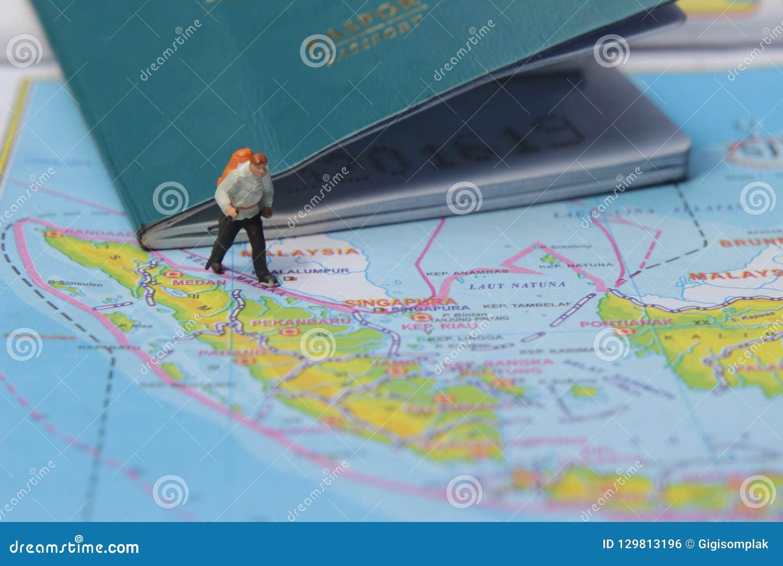 Ejemplo para el día de fiesta de la aventura, Mini Figure Hiker que camina en el atlas, pasando por el pasaporte grande