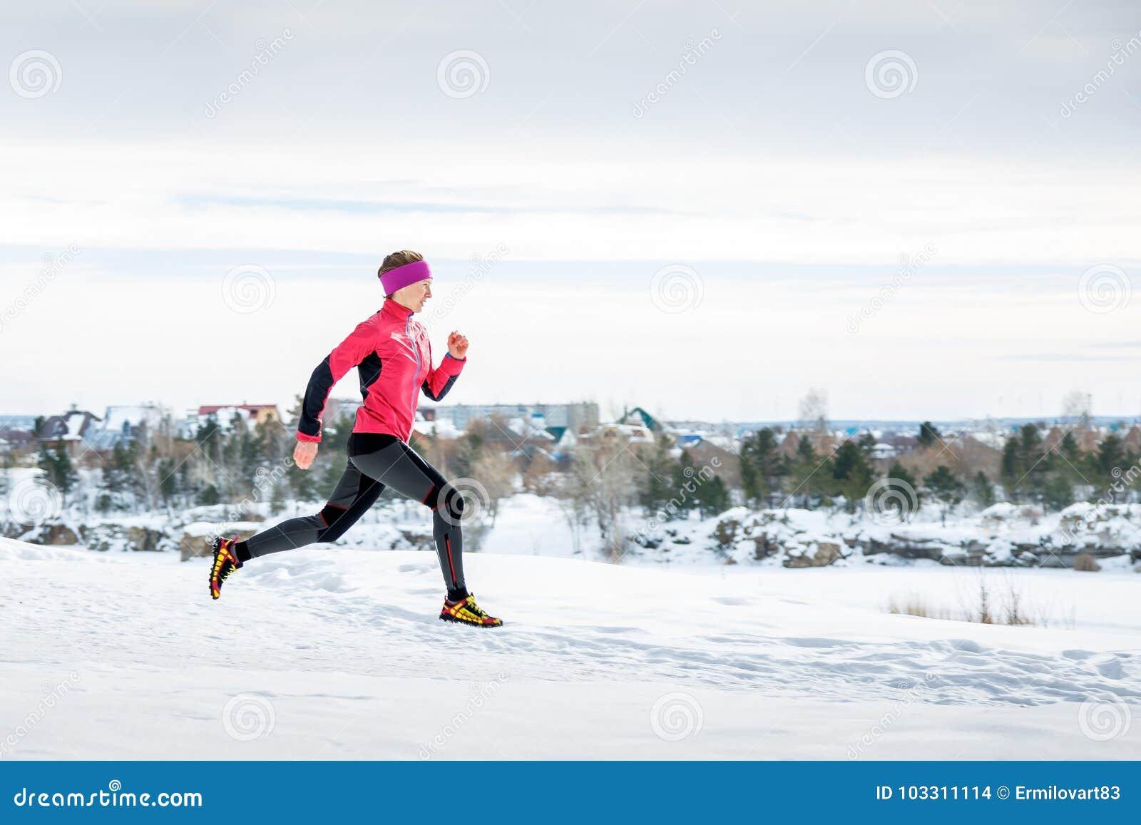 Ejercicio corriente del invierno Corredor que activa en nieve Funcionamiento modelo de la aptitud de la mujer joven en un parque