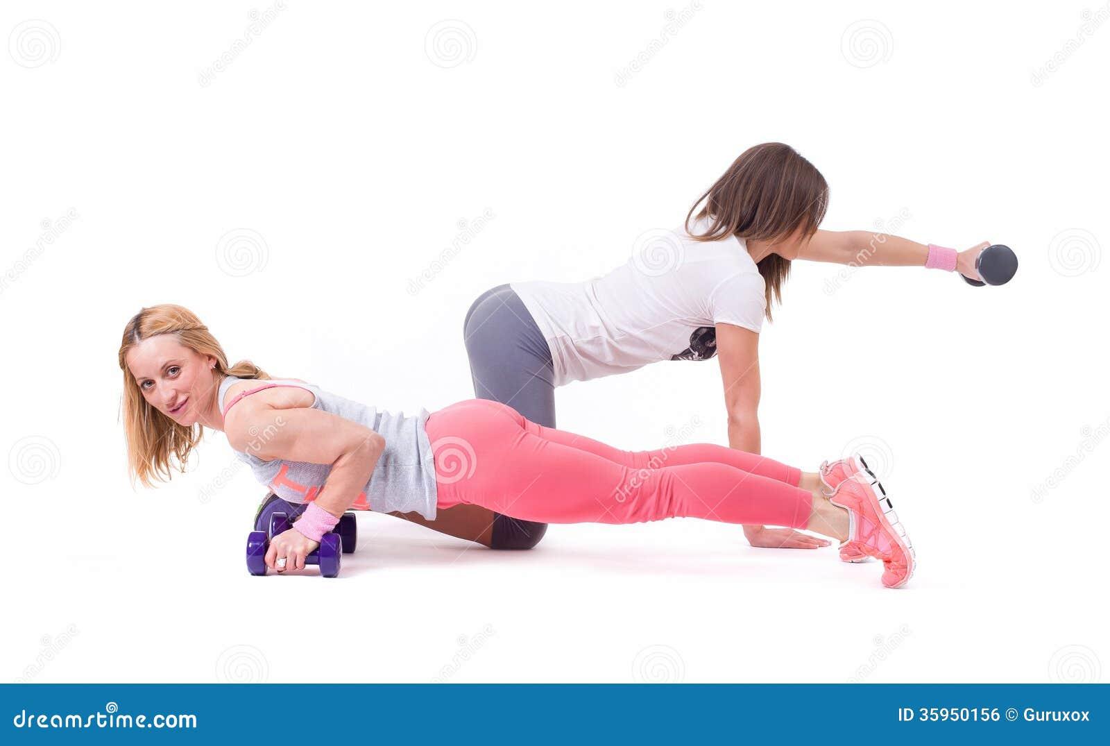 Ejercicio de la mujer de dos deportes con pesas de gimnasia