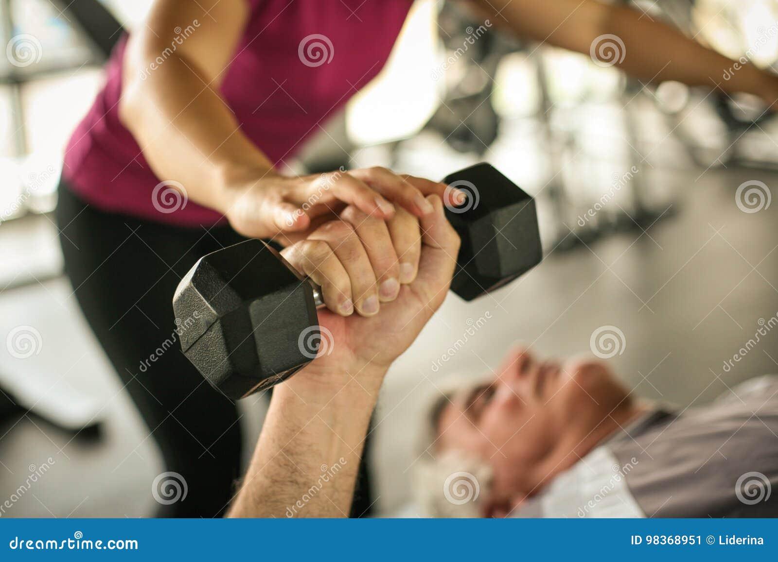 Ejercicio de trabajo del instructor personal con el hombre mayor