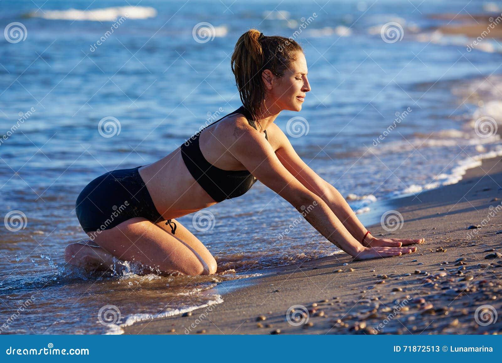 Ejercicio del entrenamiento de la yoga de Pilates al aire libre en la playa
