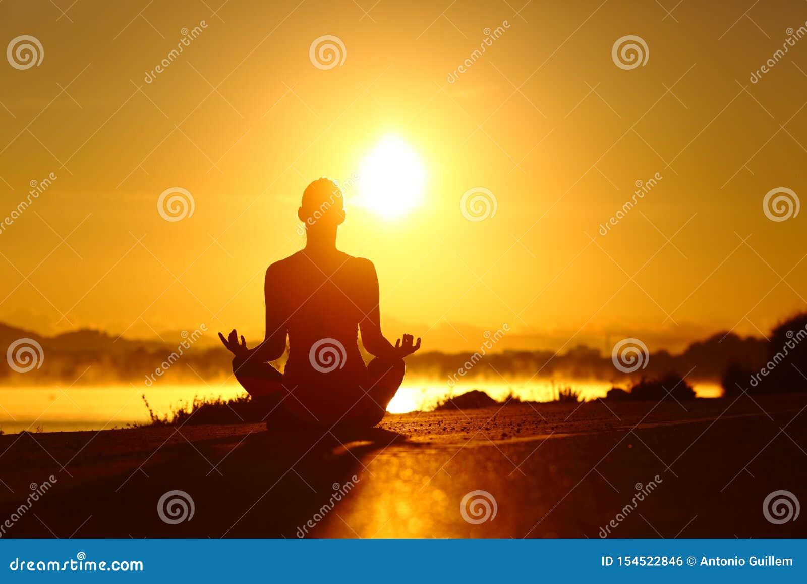 Ejercicio practicante de la yoga de la silueta de la mujer en la salida del sol