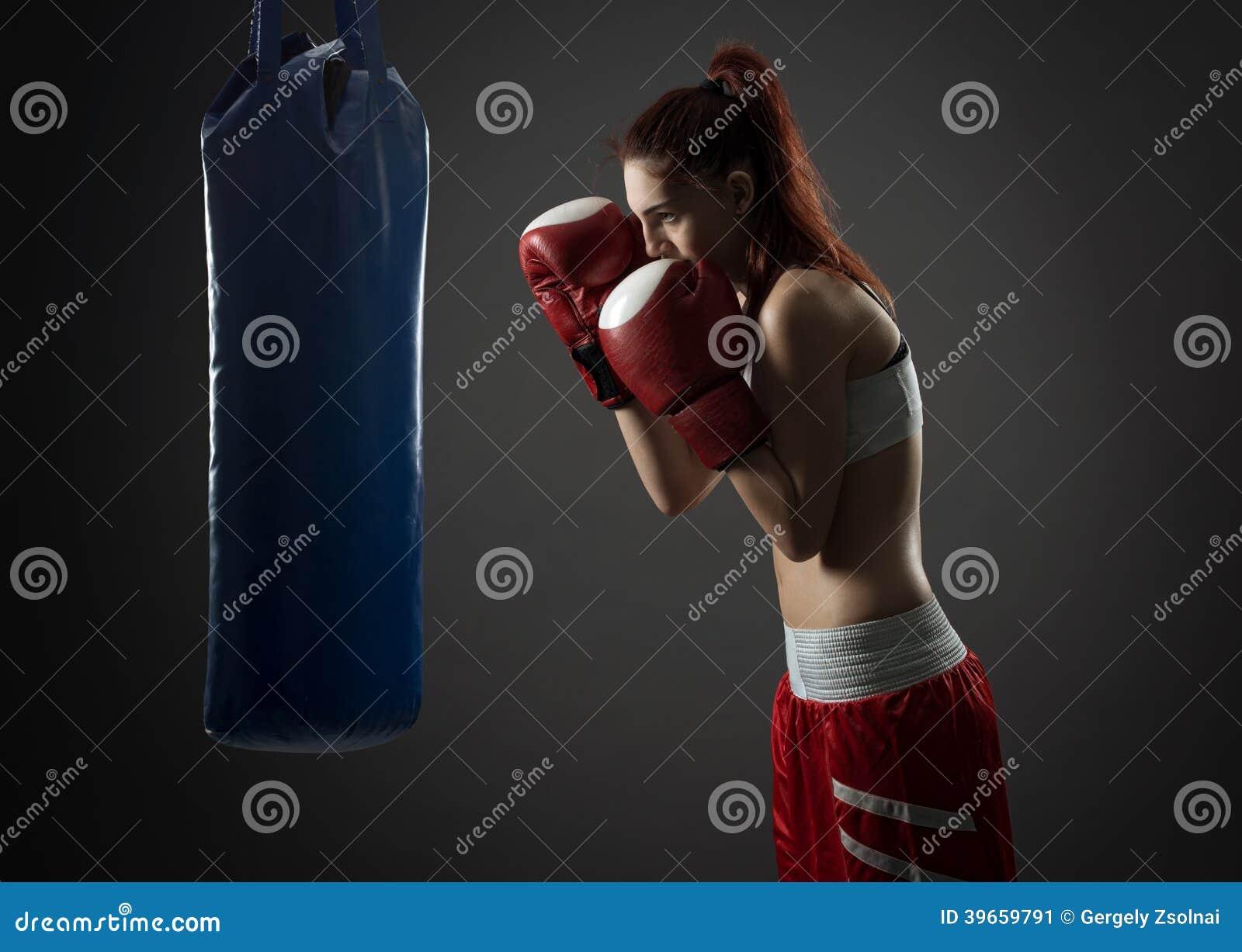 Ejercicios de la mujer del boxeo con el saco de arena