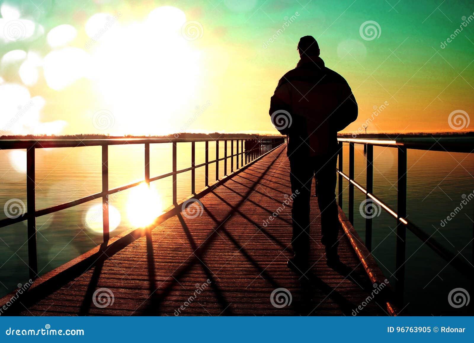 Ekranowa adra Mężczyzna sylwetki spacer na nabrzeże budowie nad morze słońce Fantastyczny ranek z jasnym niebem, gładki poziom wo