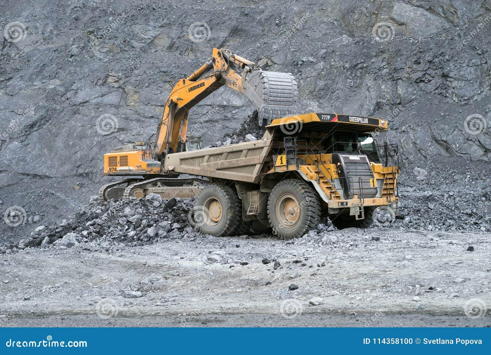 Ekskawator Liebherr ładuje kruszec w usyp ciężarówce Caterpillar w tle łup
