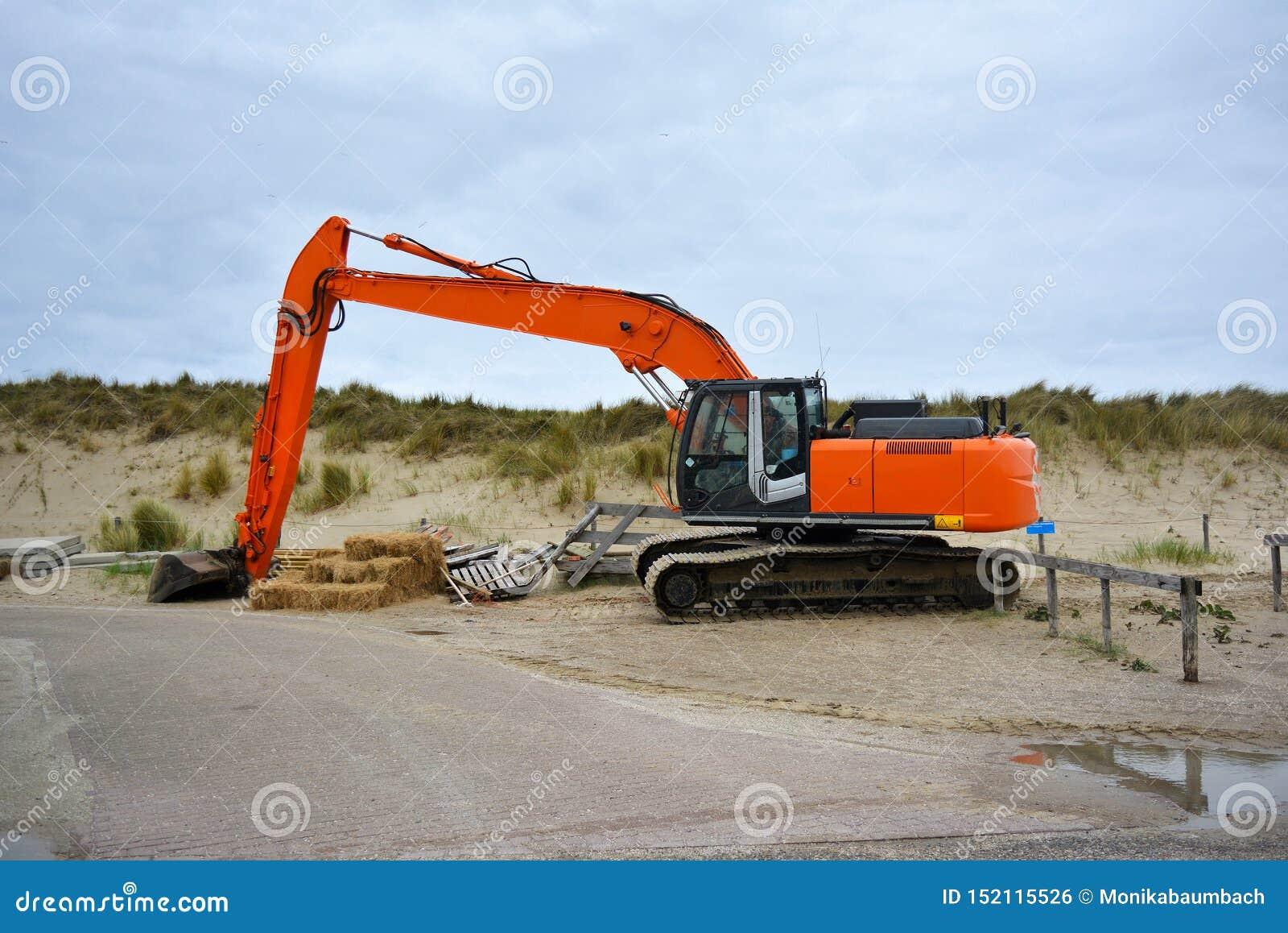 Ekskawatoru pojazd dla budować w górę piaska przy plażą przy Paal 9 po ciężkiej burzy przy Texel