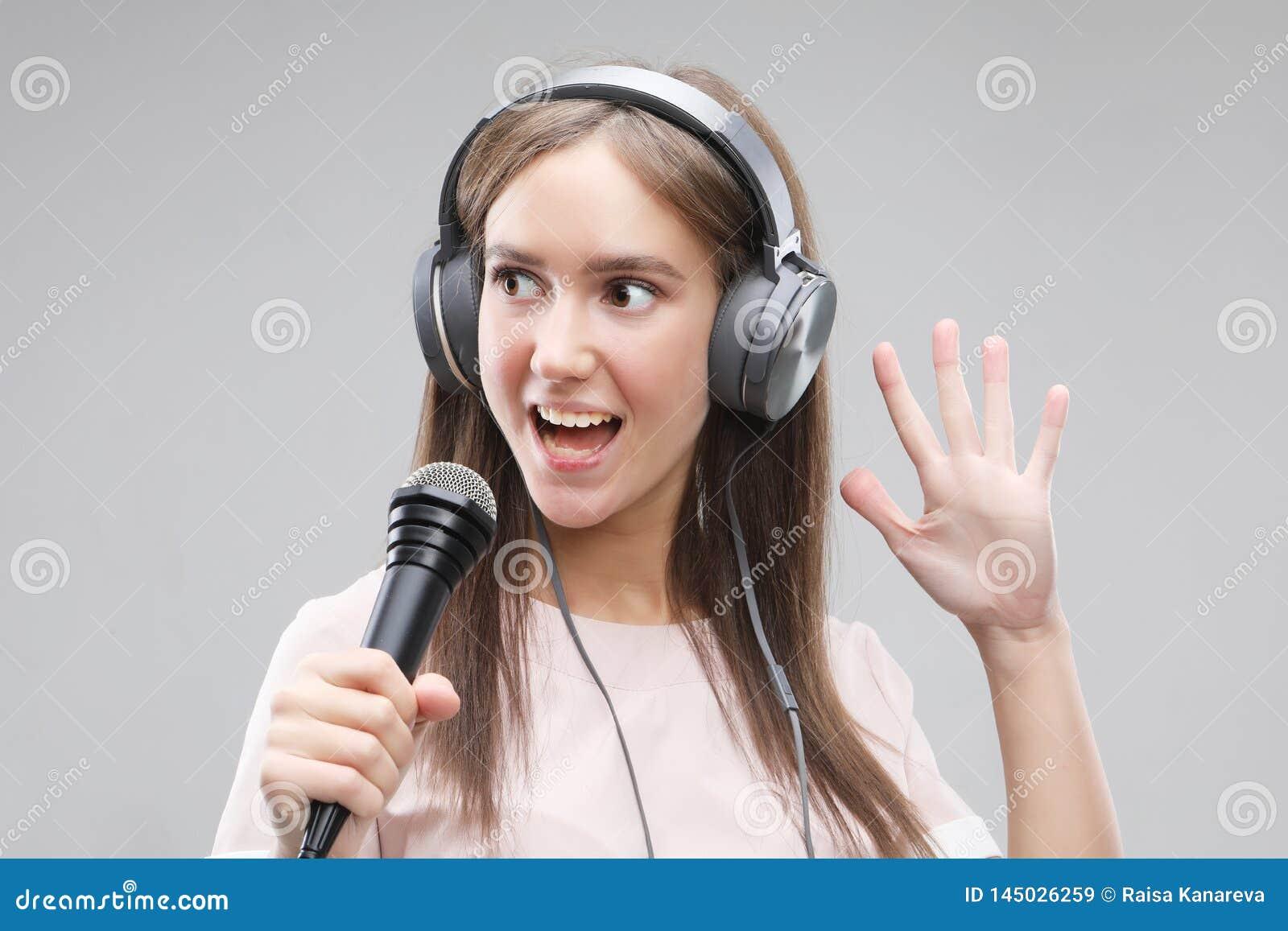 Ekspresyjny dziewczyna ?piew z mikrofonem i he?mofonami
