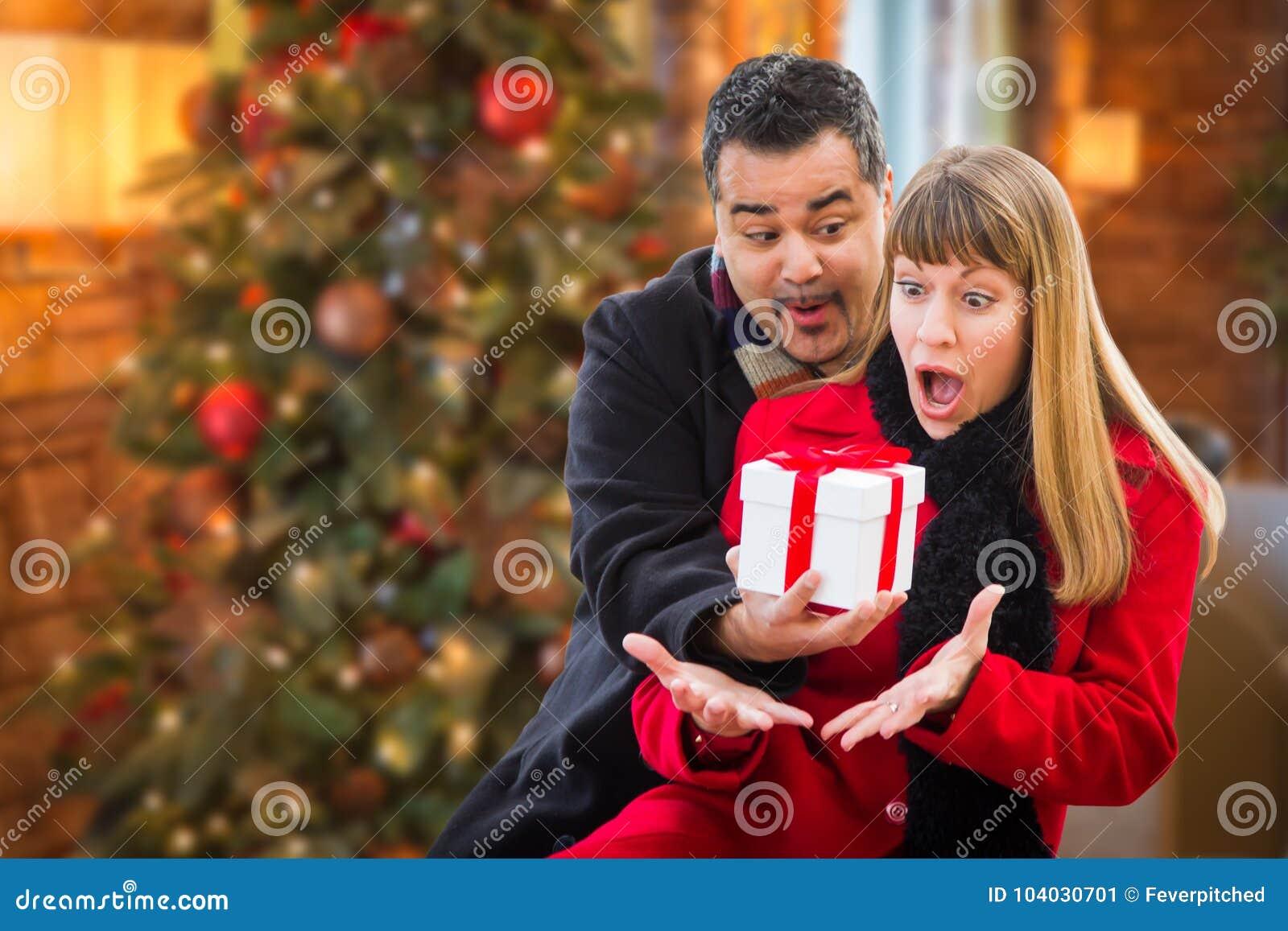 Ekstatische Mischrasse-Paare, die Weihnachten vor verziertem Baum teilen