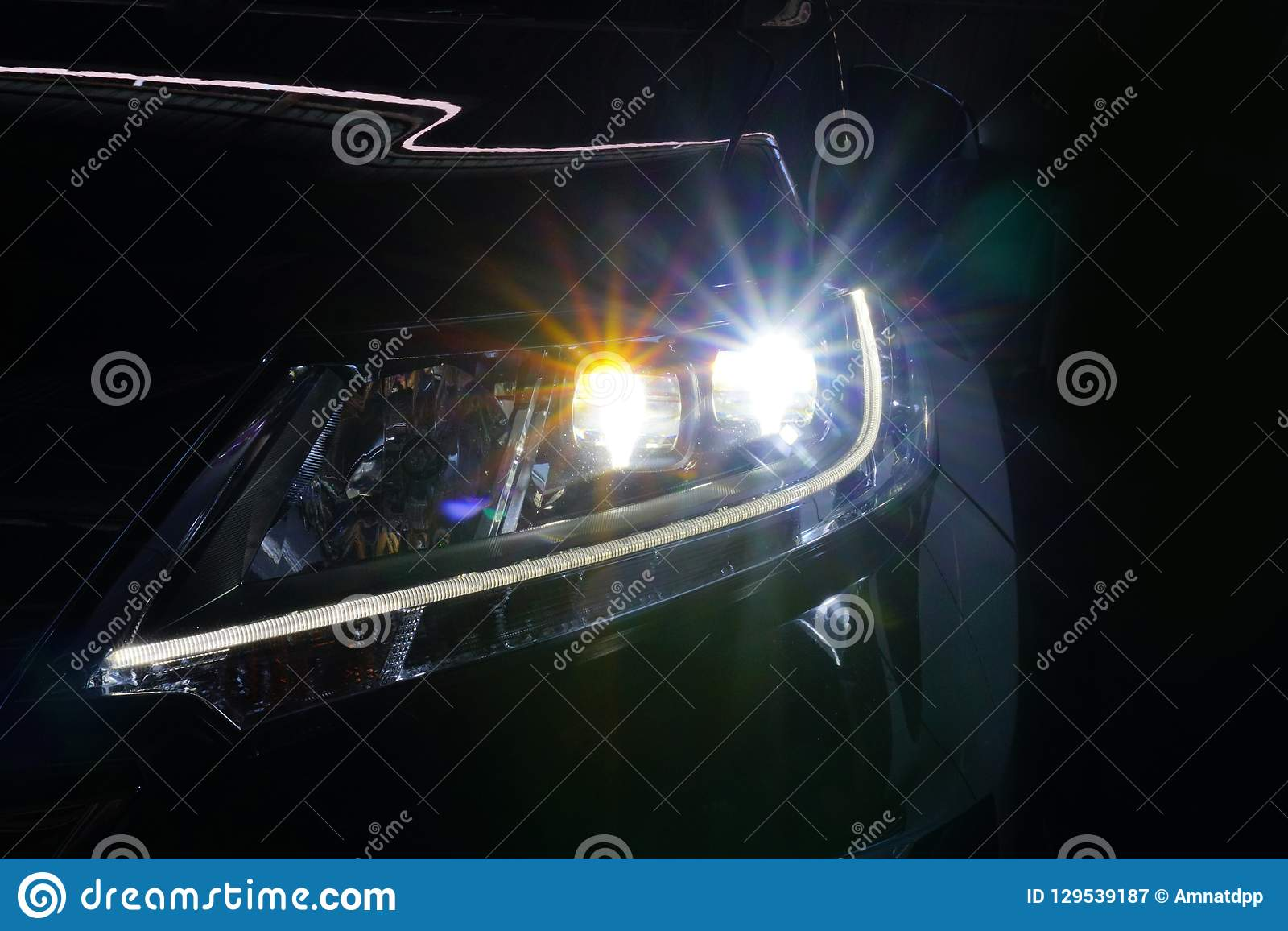 El ángel observa la lente de la óptica de la linterna del xenón que brilla intensamente