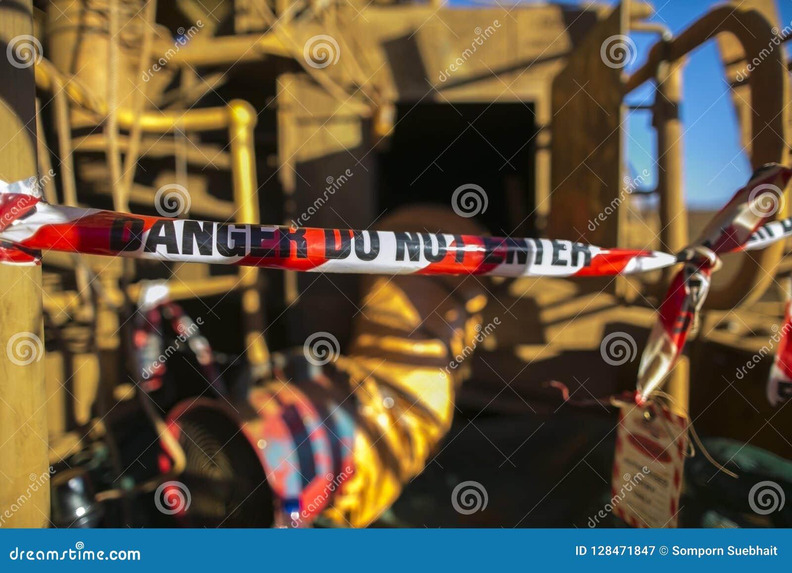 El área roja y blanca del peligro de la cinta de la barricada de exclusión en la puerta de entrada confinada del espacio autorizó