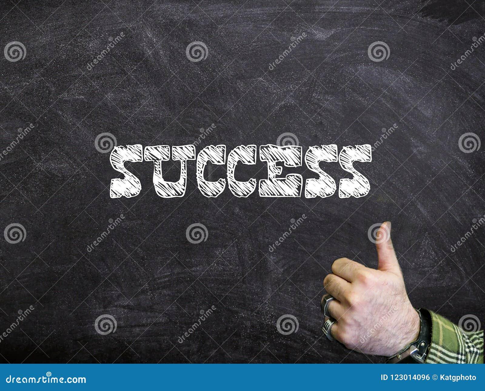 El éxito escrito en una pizarra con los pulgares sube la muestra