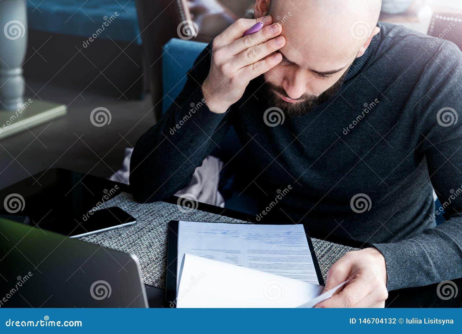 El abogado de sexo masculino serio se sienta en caf? en la tabla y lee el contrato antes de firmar del cliente El Freelancer trab