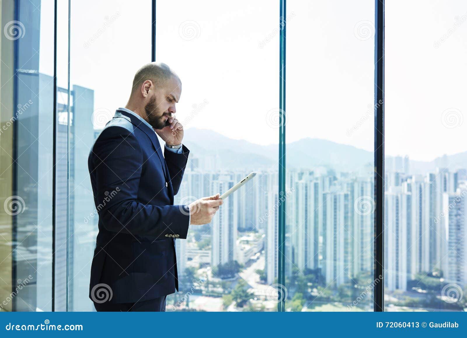 El abogado joven con la cara seria y la tableta digital a disposición está hablando en el teléfono móvil con el cliente