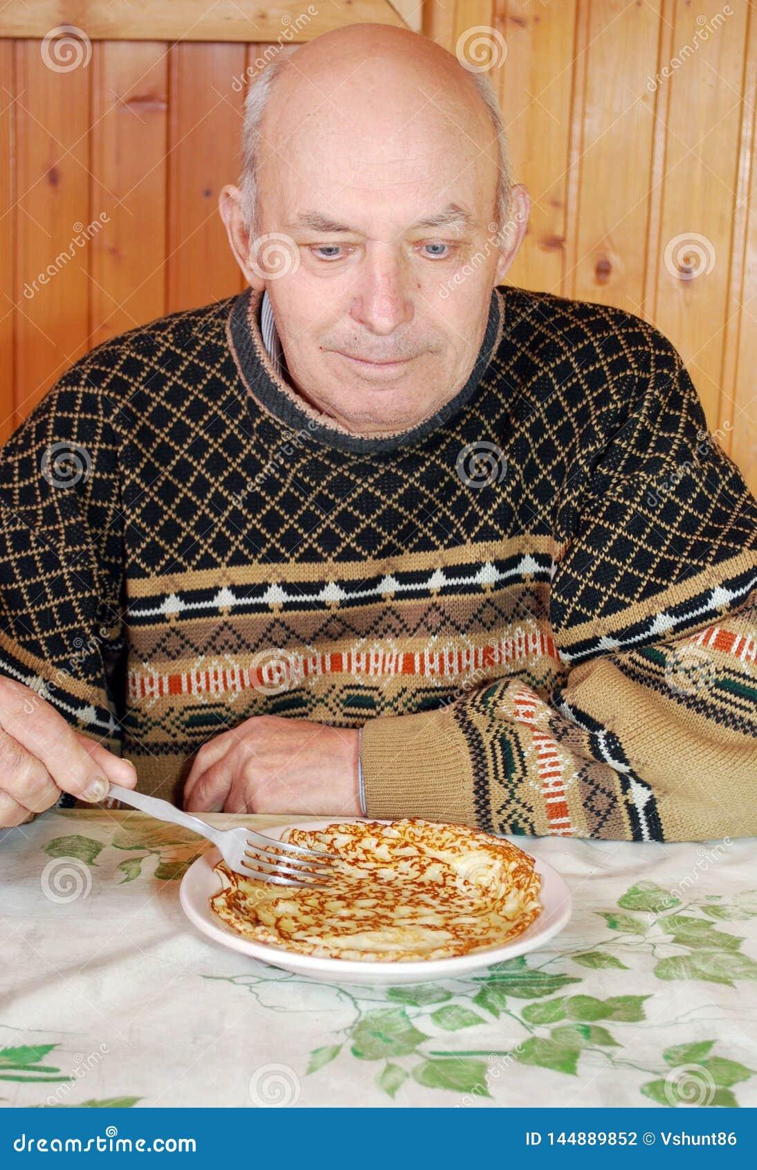 El abuelo se sentó en una tabla y come la crepe caliente con apetito