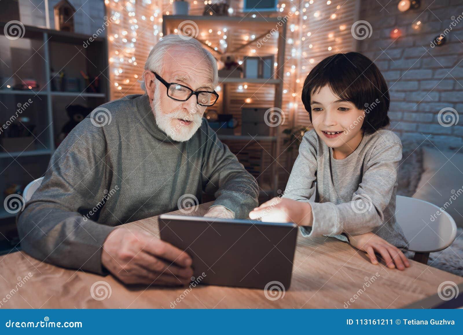 El abuelo y el nieto están mirando película en la tableta en la noche en casa