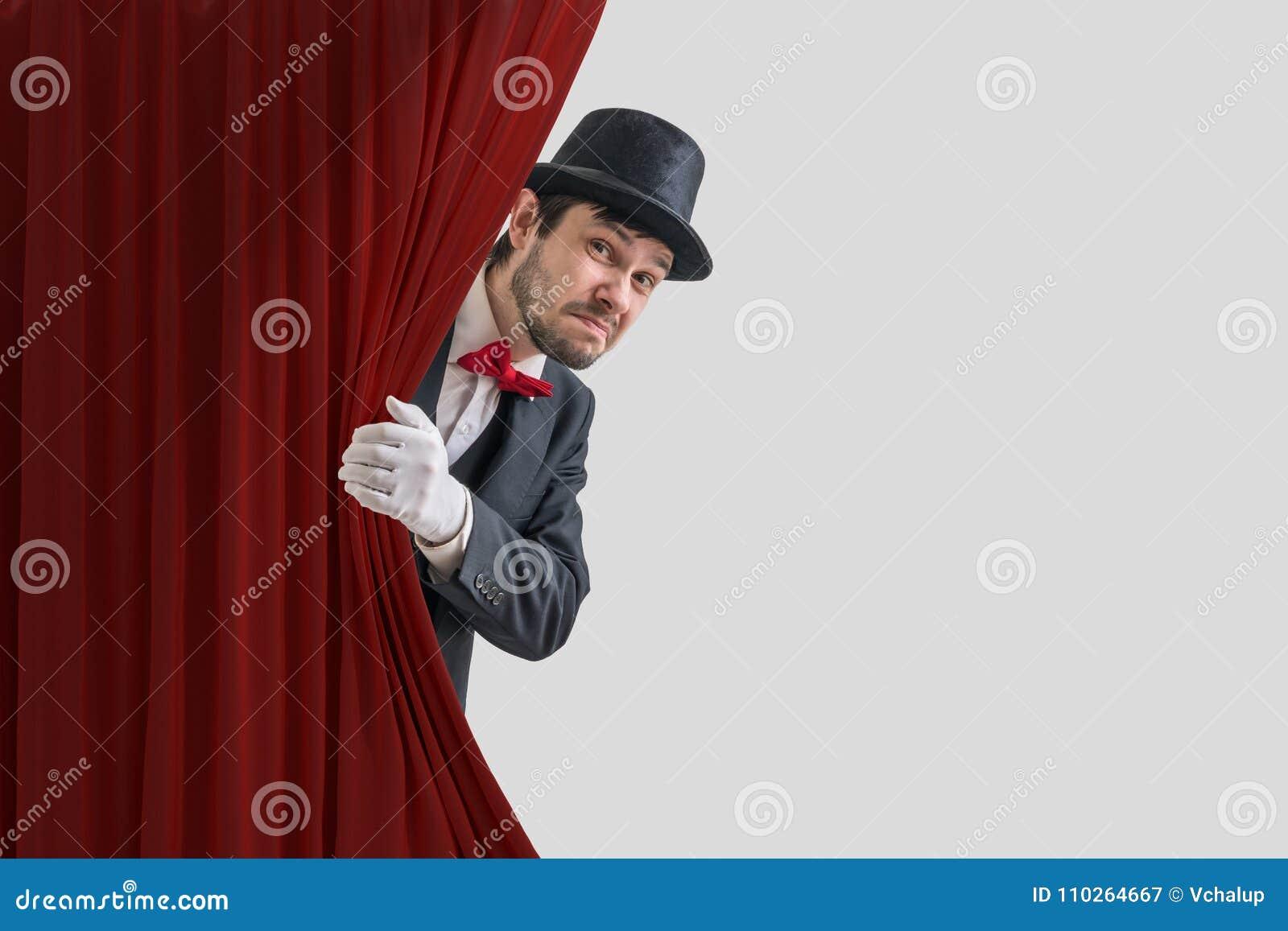 El actor o el ilusionista nervioso está ocultando detrás de la cortina roja en teatro
