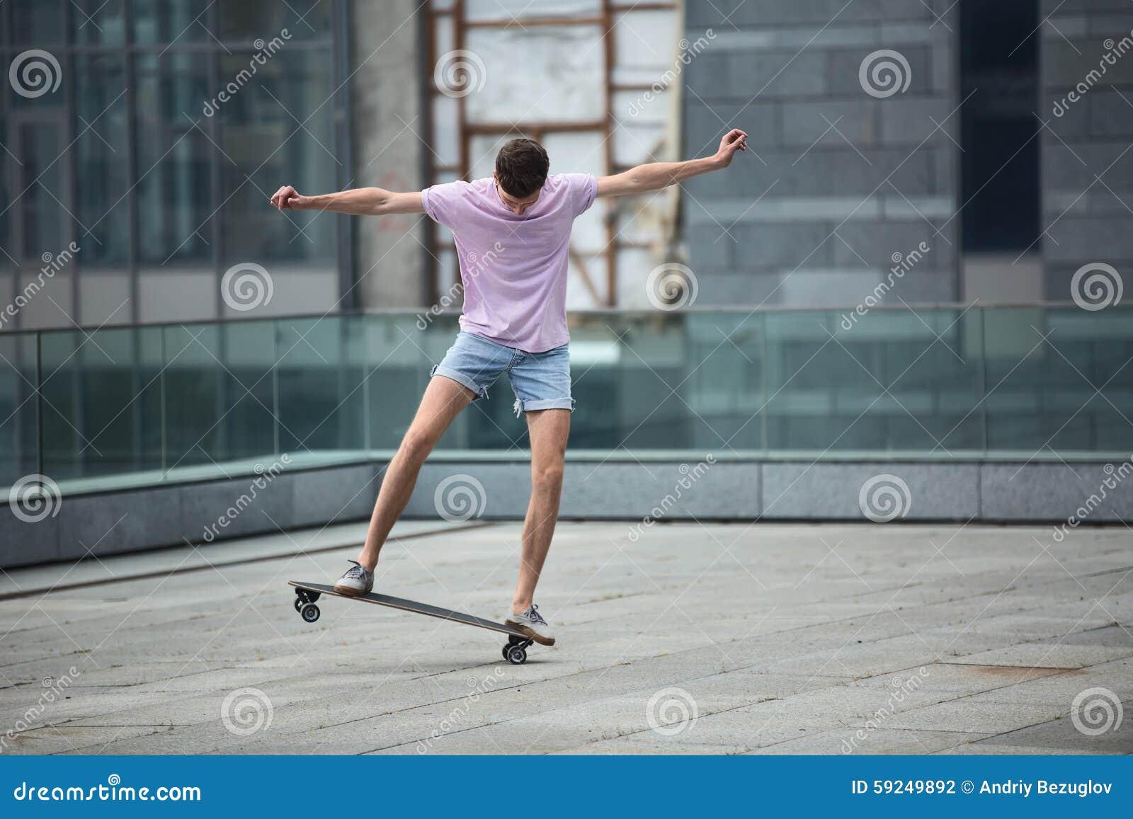 El adolescente elegante hace trucos de un longboard